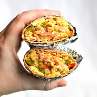 Holding a split in half breakfast burrito.