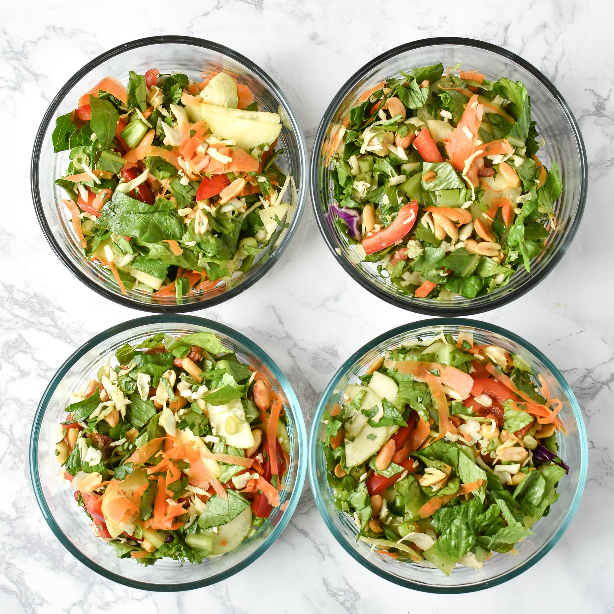 meal prep chopped thai salad in four glass pyrex bowls