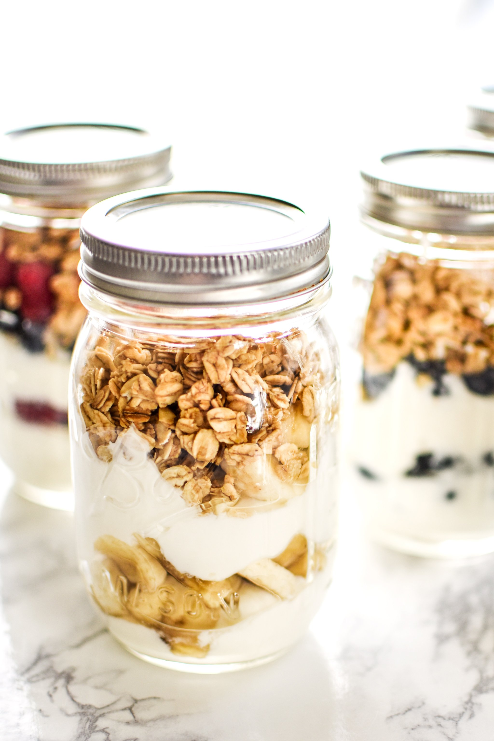 Greek yogurt, fruit and granola meal prepped into mason jar parfaits.