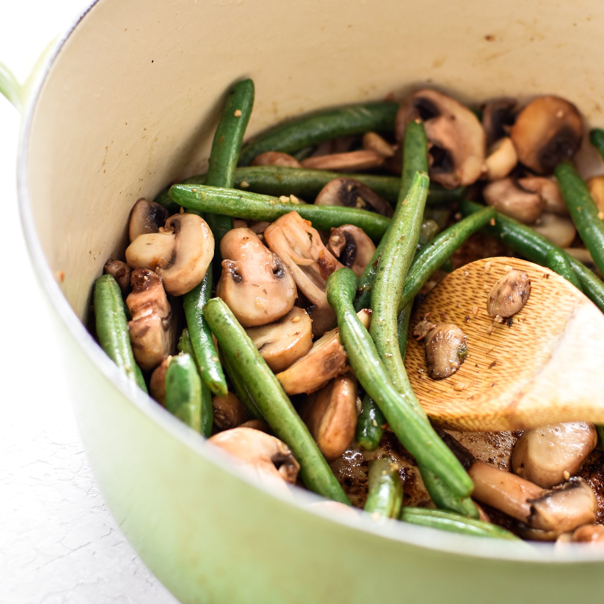 Mushrooms and green beans cooking the Dutch Oven. ThisOne-Pot Pesto Chicken and Rice is the perfect idea if you're short on dinner prep time. - ProjectMealPlan.com