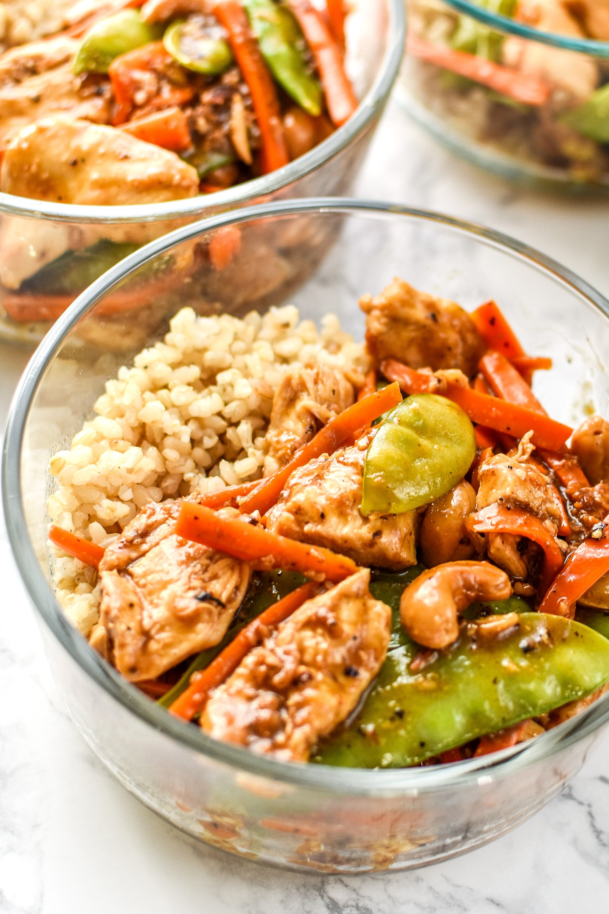 Cashew chicken meal prep with carrots and snow peas.