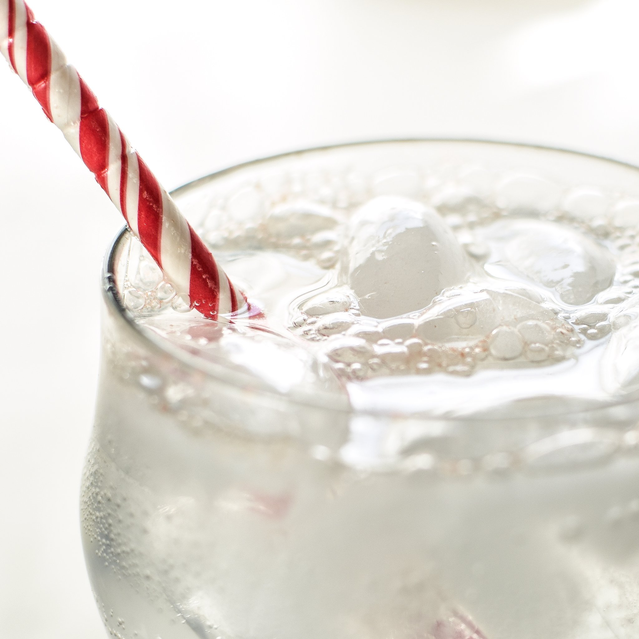 A cold fizzy beverage with lots of bubbles at the top and a red and white candy cane striped straw. Homemade LaCroix