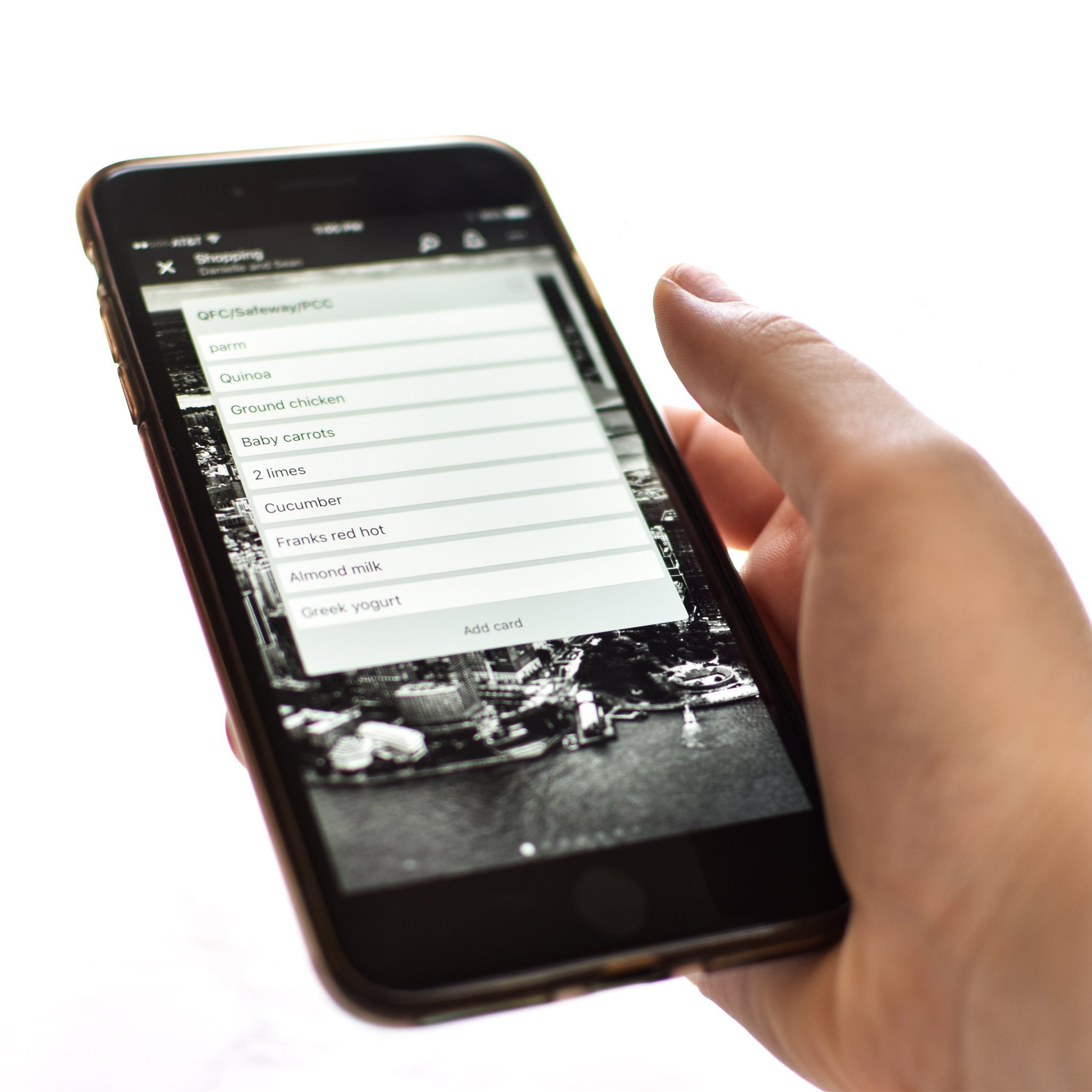 Holding a phone with a shopping list displayed using the app Trello.