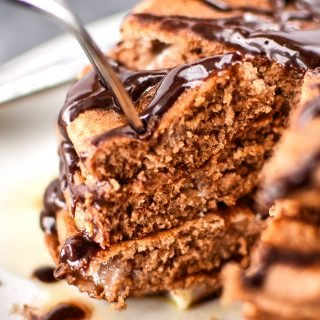 A fork piercing a big stack of Double Chocolate Peppermint Protein Pancakes drizzled with chocolate syrup.