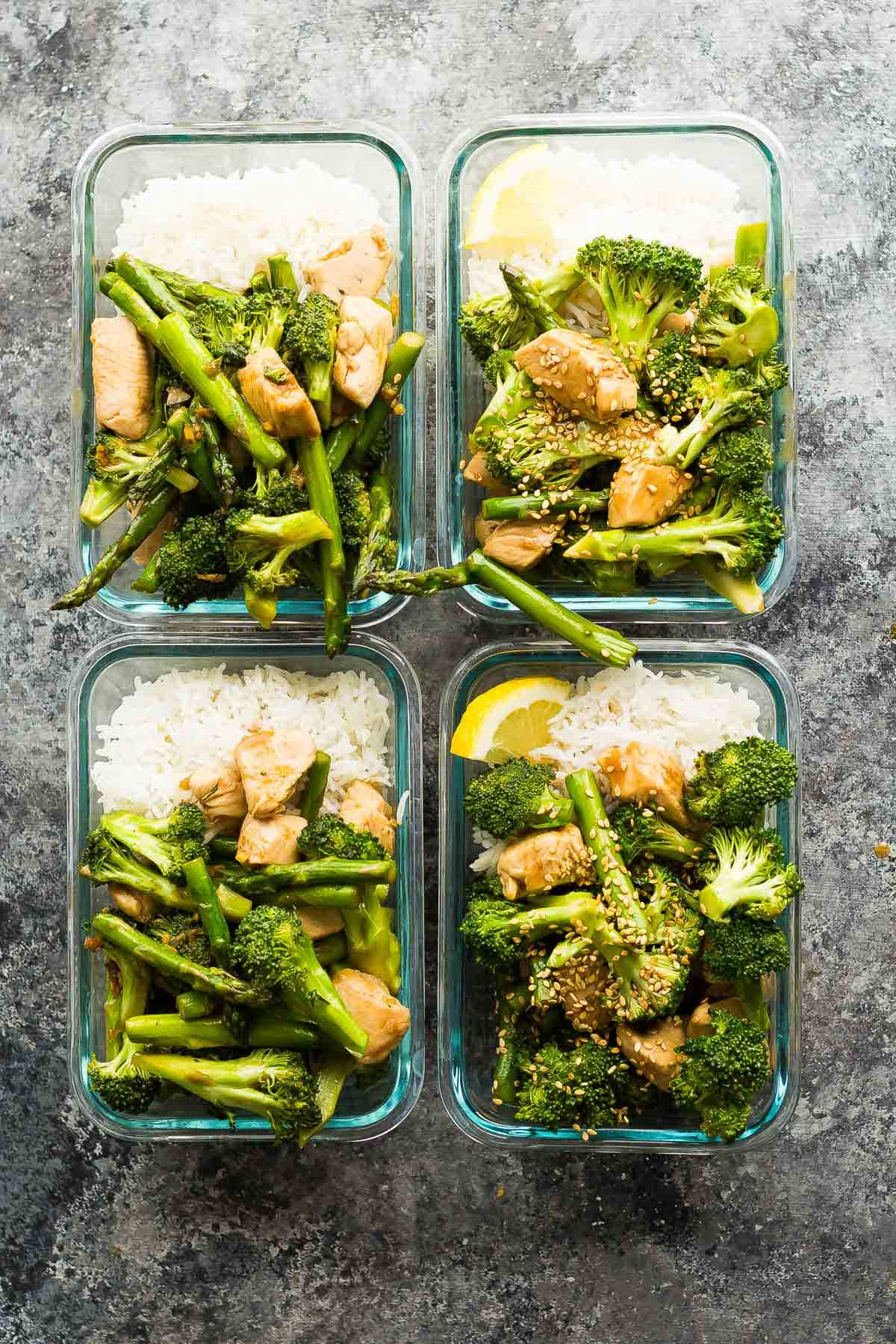 Four bowls of asparagus broccoli chicken stir fry with rice.