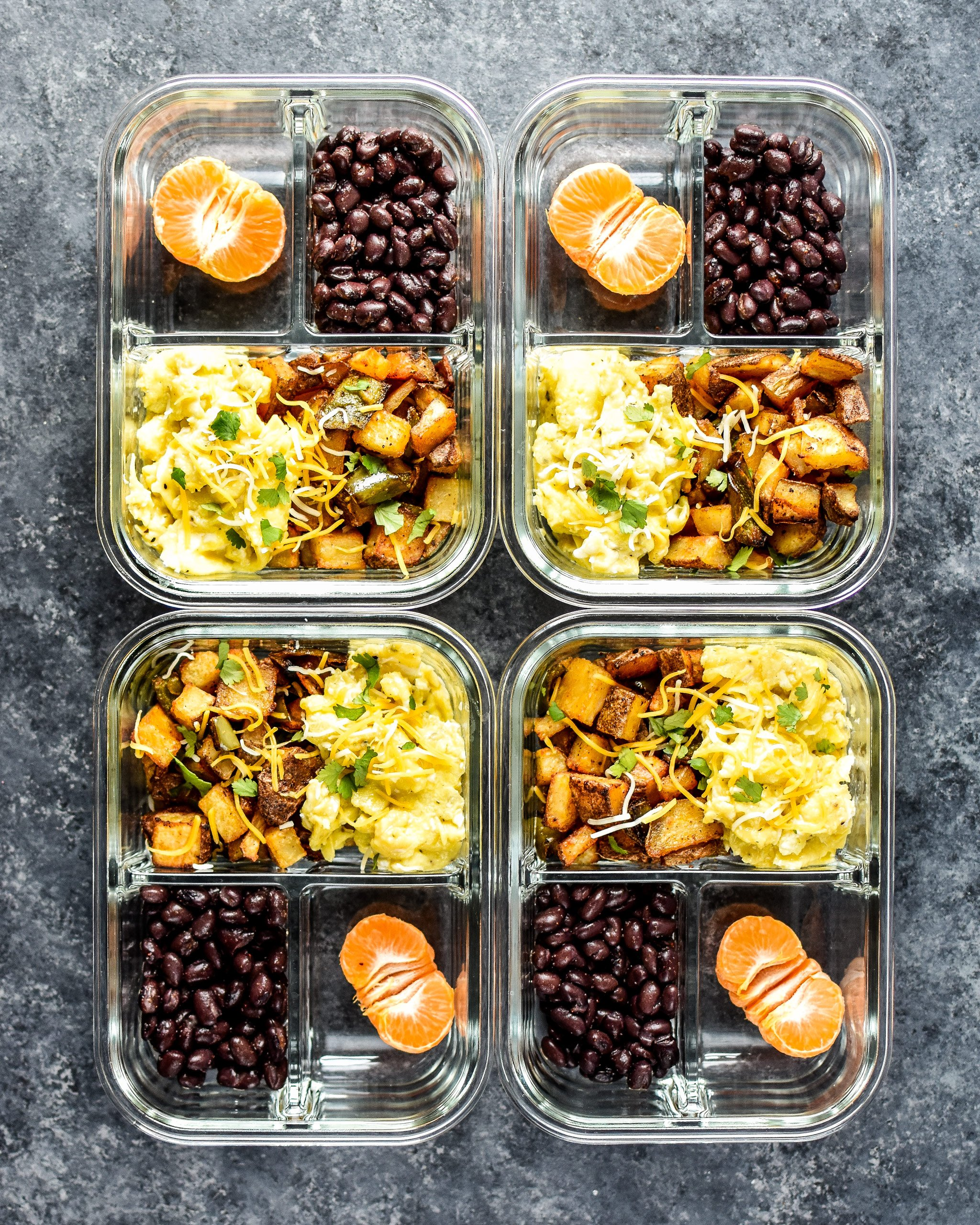 Four meal prep containers with potatoes, eggs, black beans and half a mandarin.