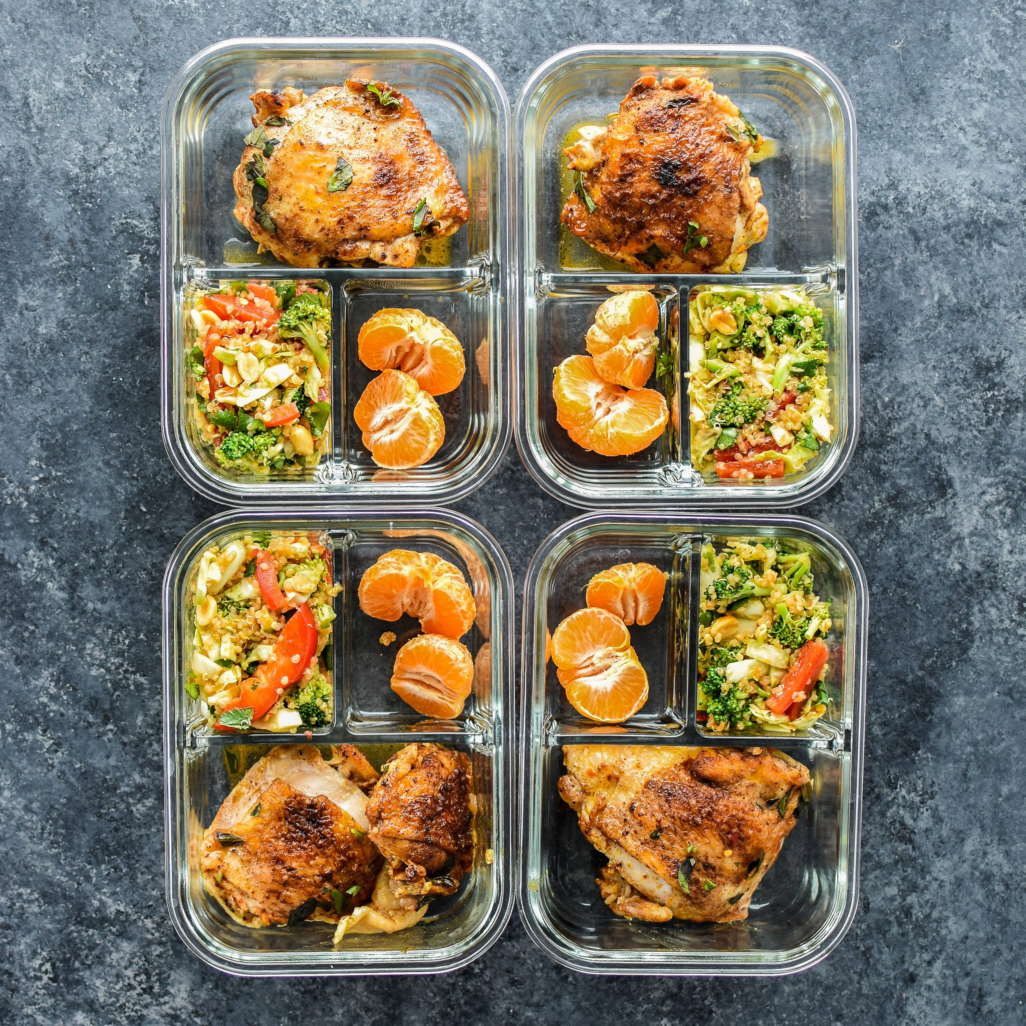 Meal prepped chicken thighs with asian quinoa salad and mandarins.