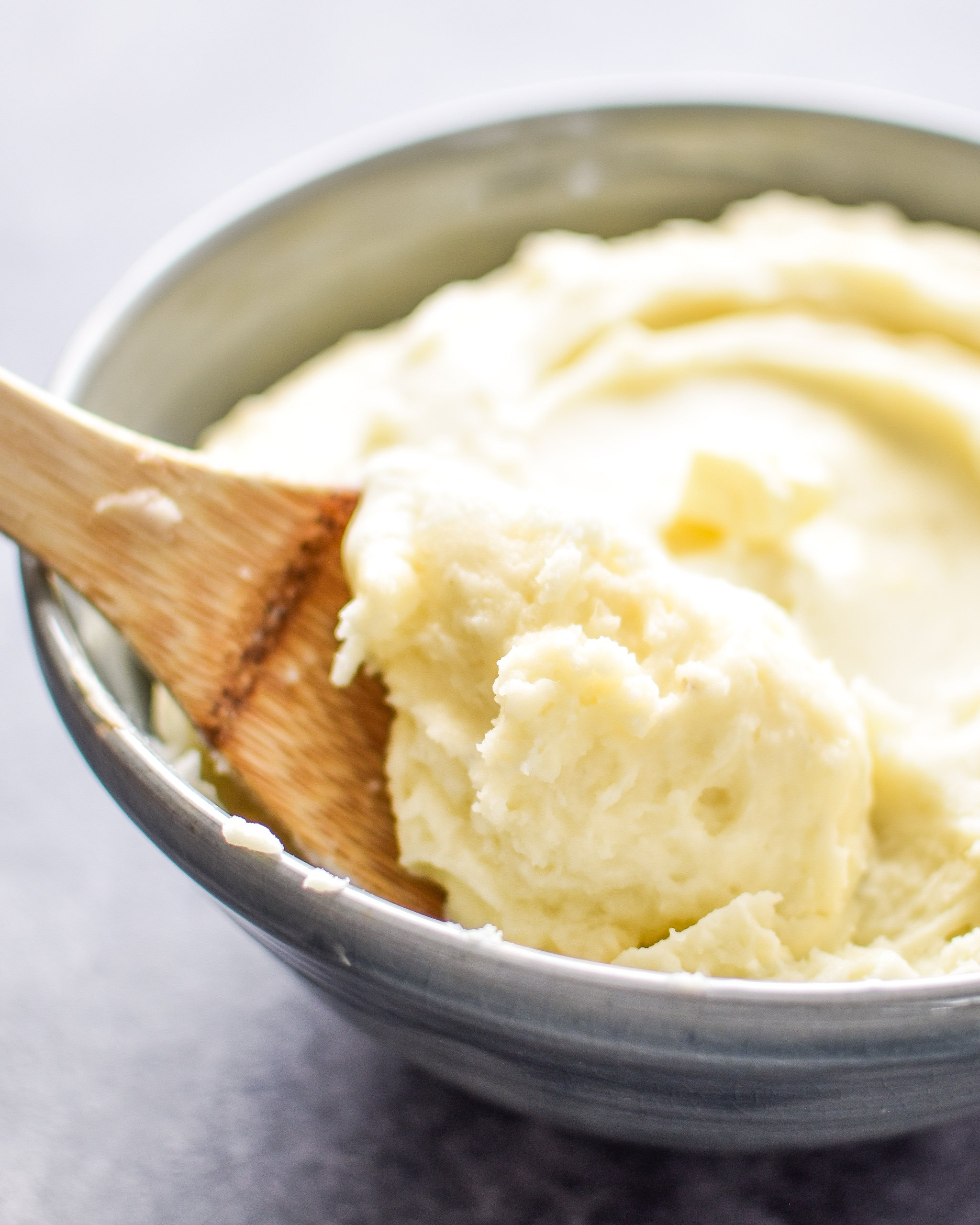 A spoonful of mashed potatoes resting in a dish of mashed potatoes.