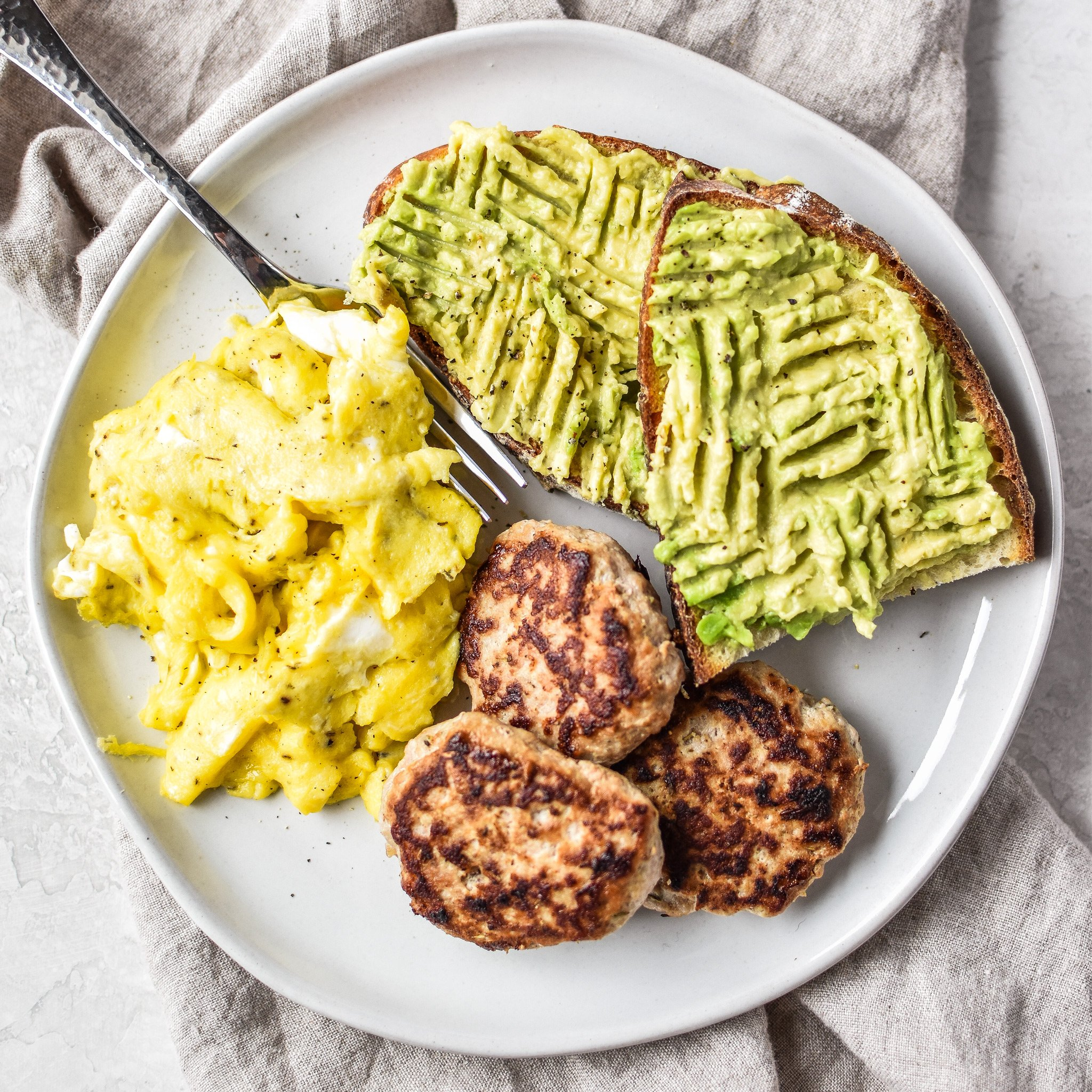 Plate of ground turkey breakfast sausage patties, scrambled eggs and avocado toast.