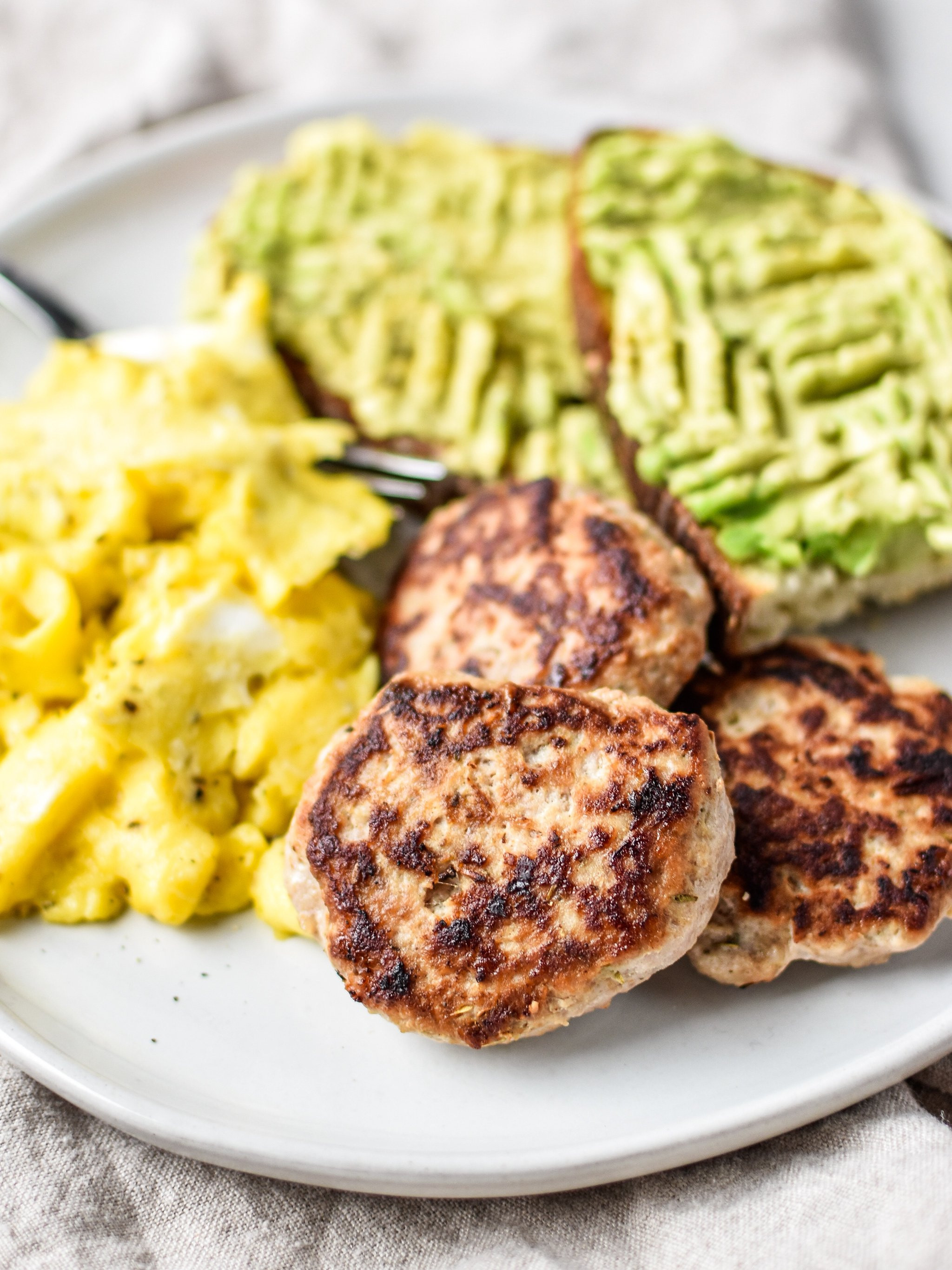 A plate of ground turkey breakfast sausage patties with eggs and avocado toast.