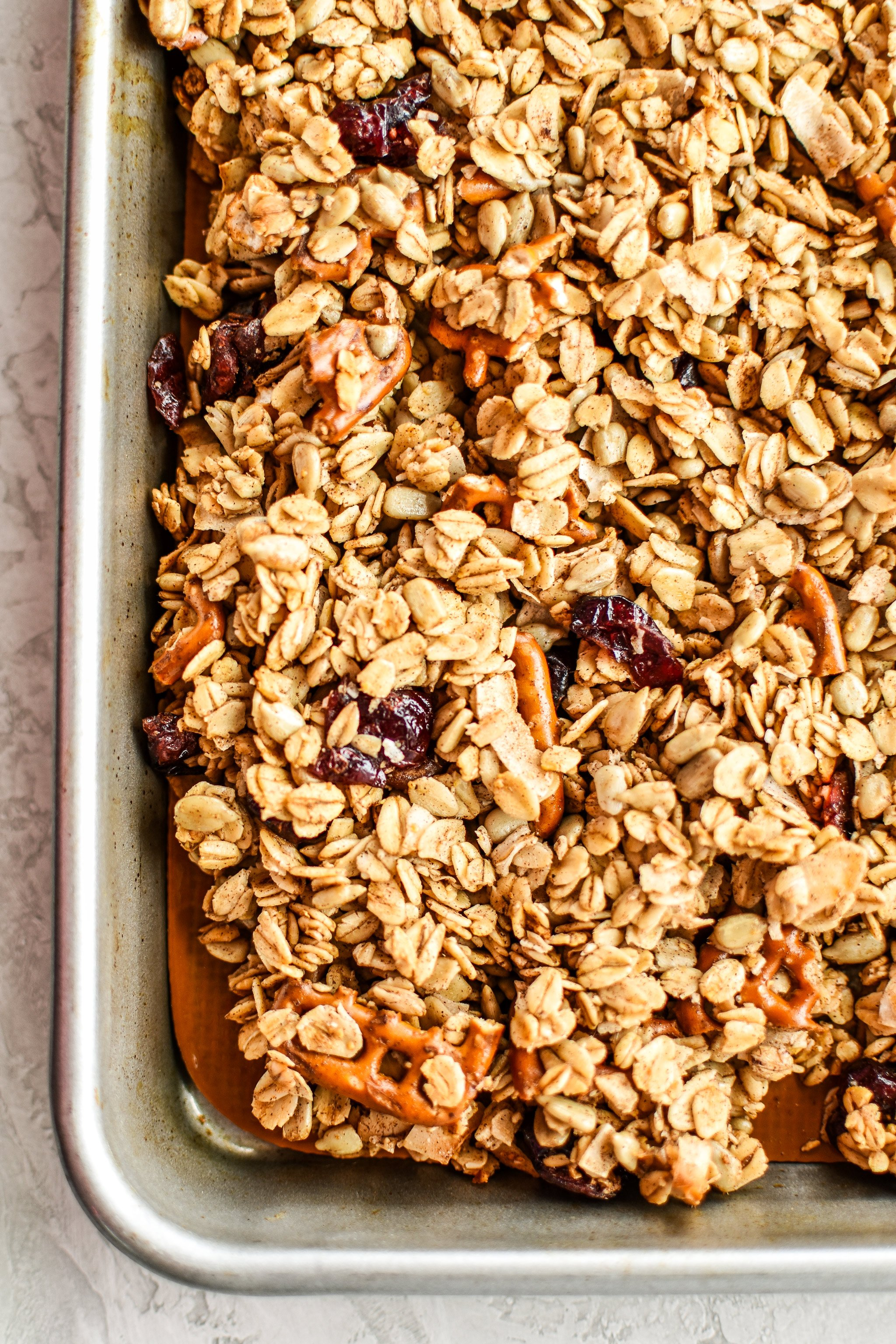 A sheet pan with cooked granola cooling.