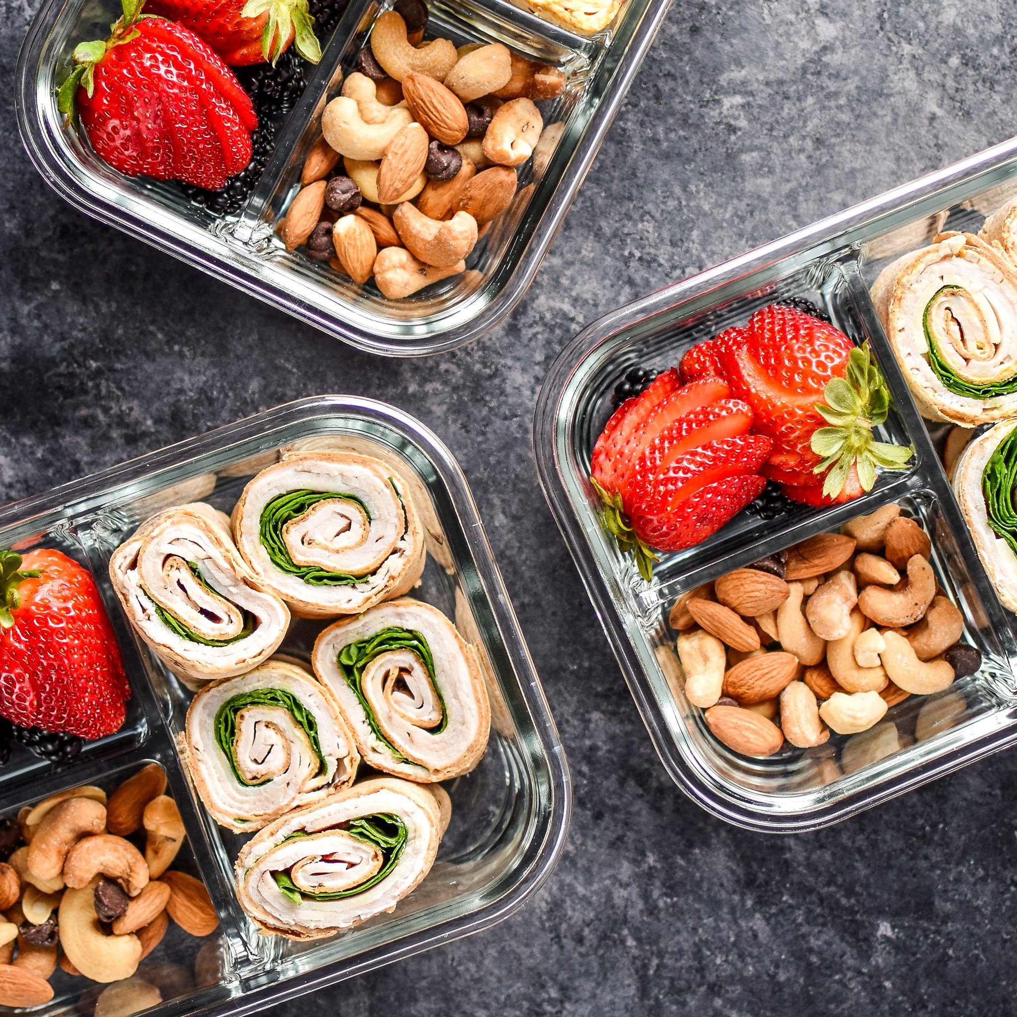 Top view of three Easy Turkey Pinwheel Meal Prep lunches with pinwheels, berries and nuts.