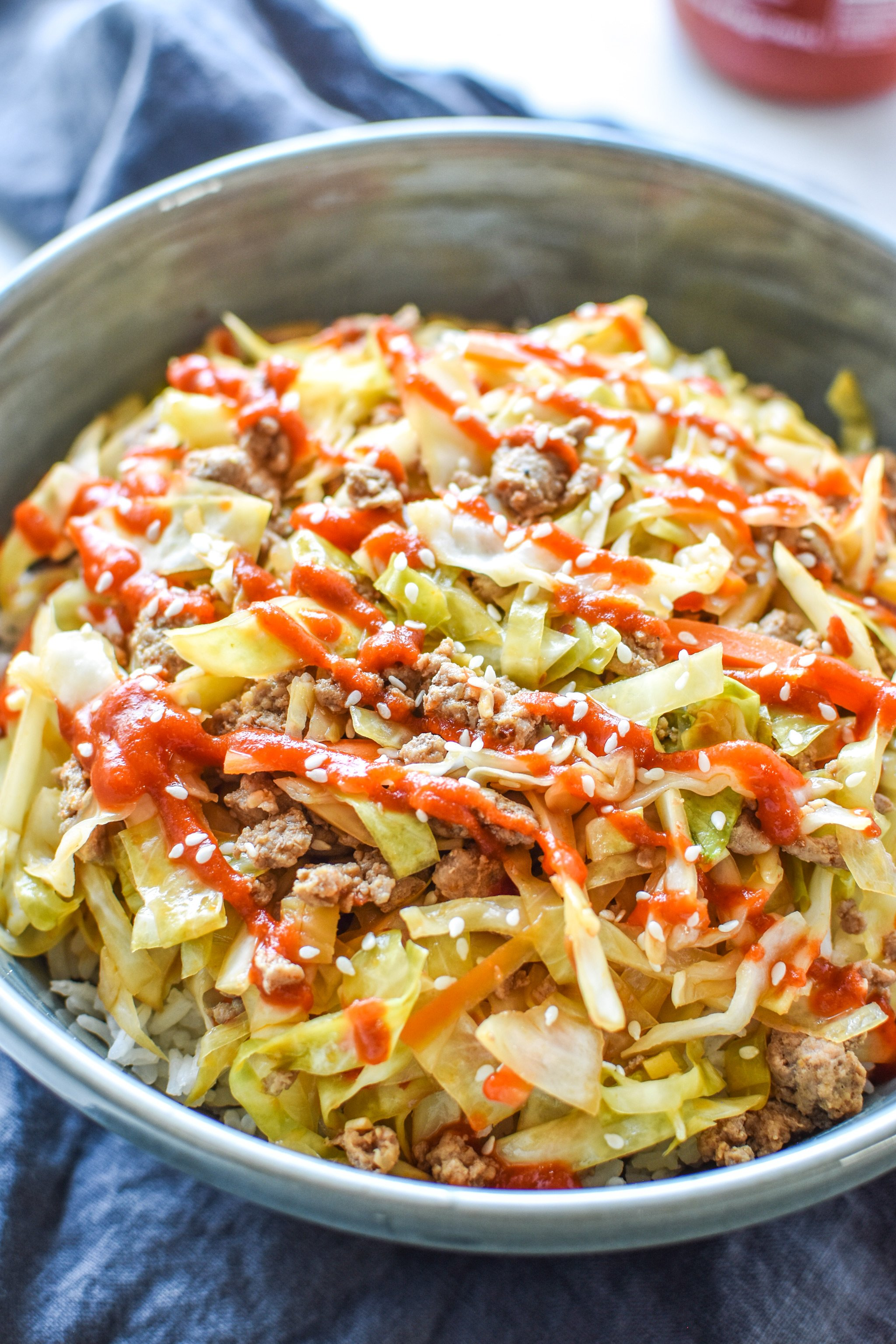 A bowl of spicy ground turkey cabbage stir fry served over rice with sriracha on top.