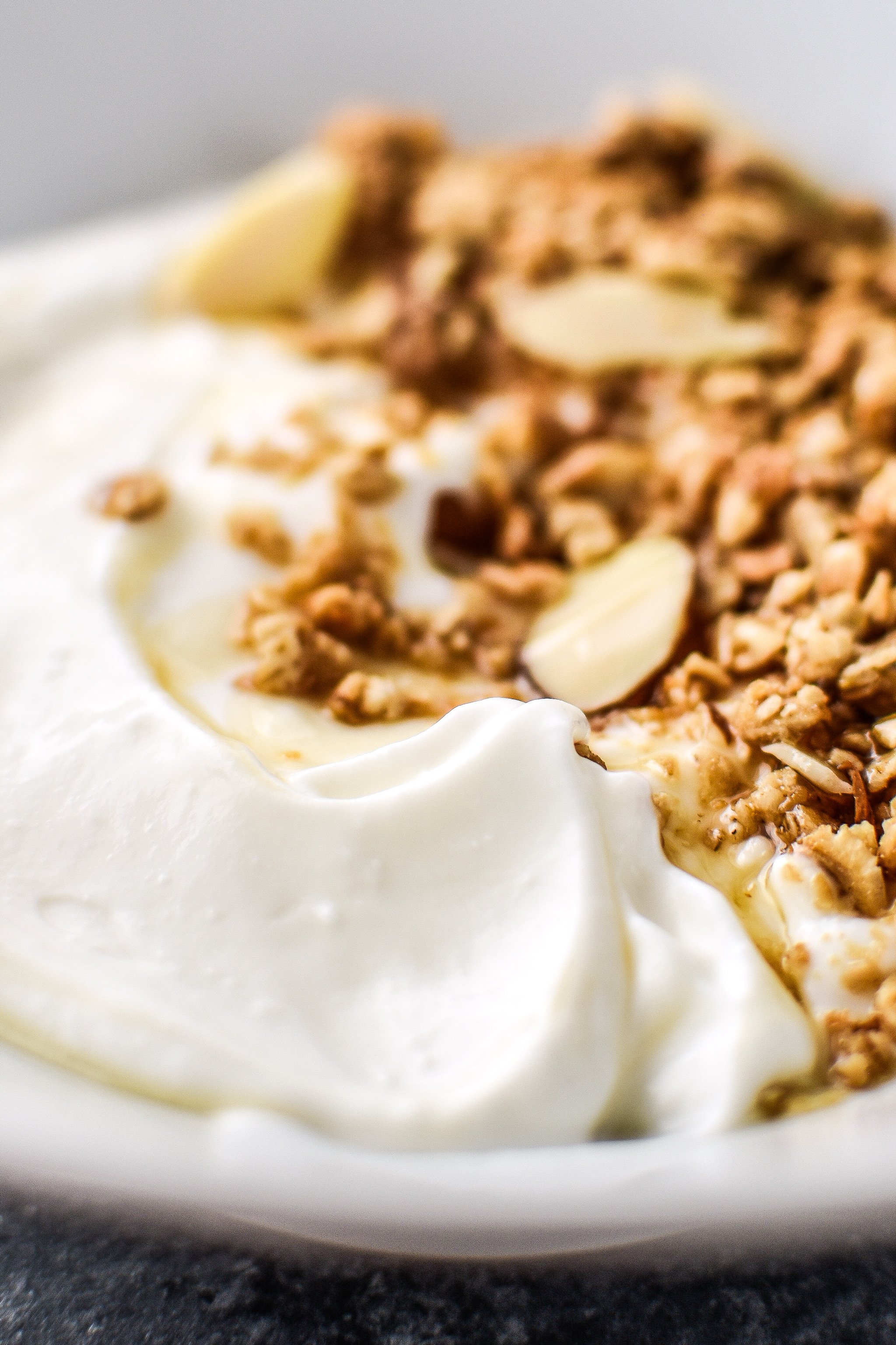 Freshly made yogurt in a bowl with granola and thin maple drizzle.