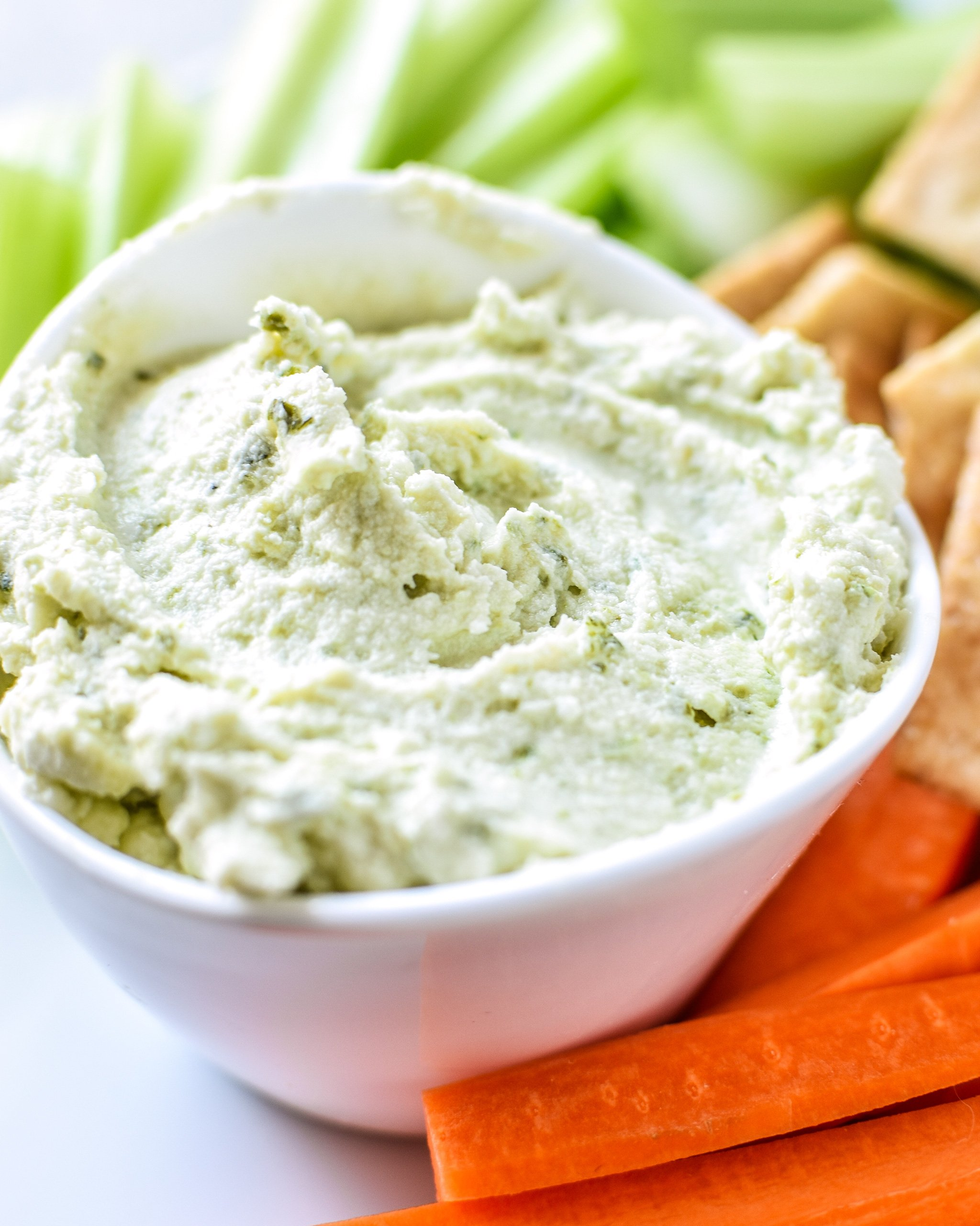 A cup of 3-Ingredient Pesto Goat Cheese Dip with carrots, celery and crackers.