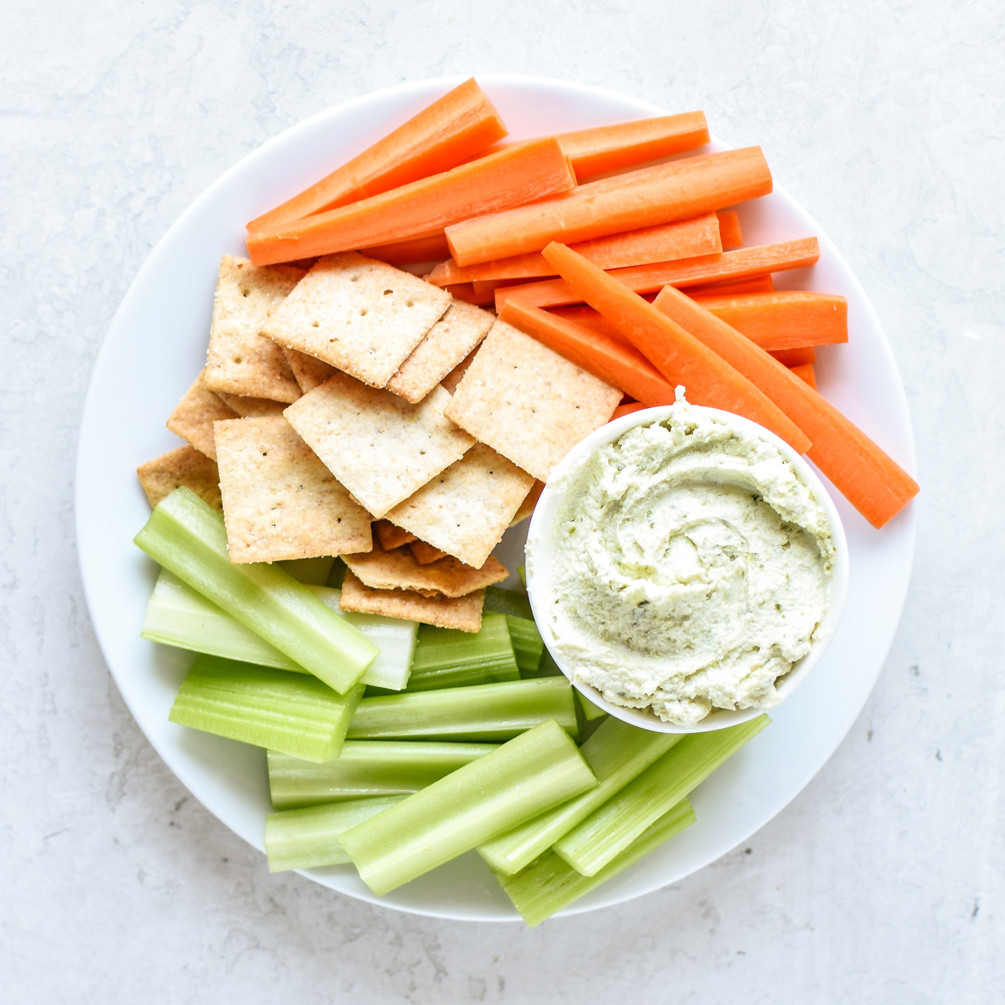 A bowl of 3 Ingredient Pesto Goat Cheese Dip with carrots, crackers and celery.
