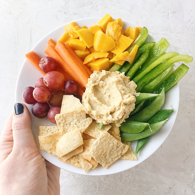 A simple no-heat lunch with grapes, pita chips, hummus, mango, snap peas, bell pepper and carrots.