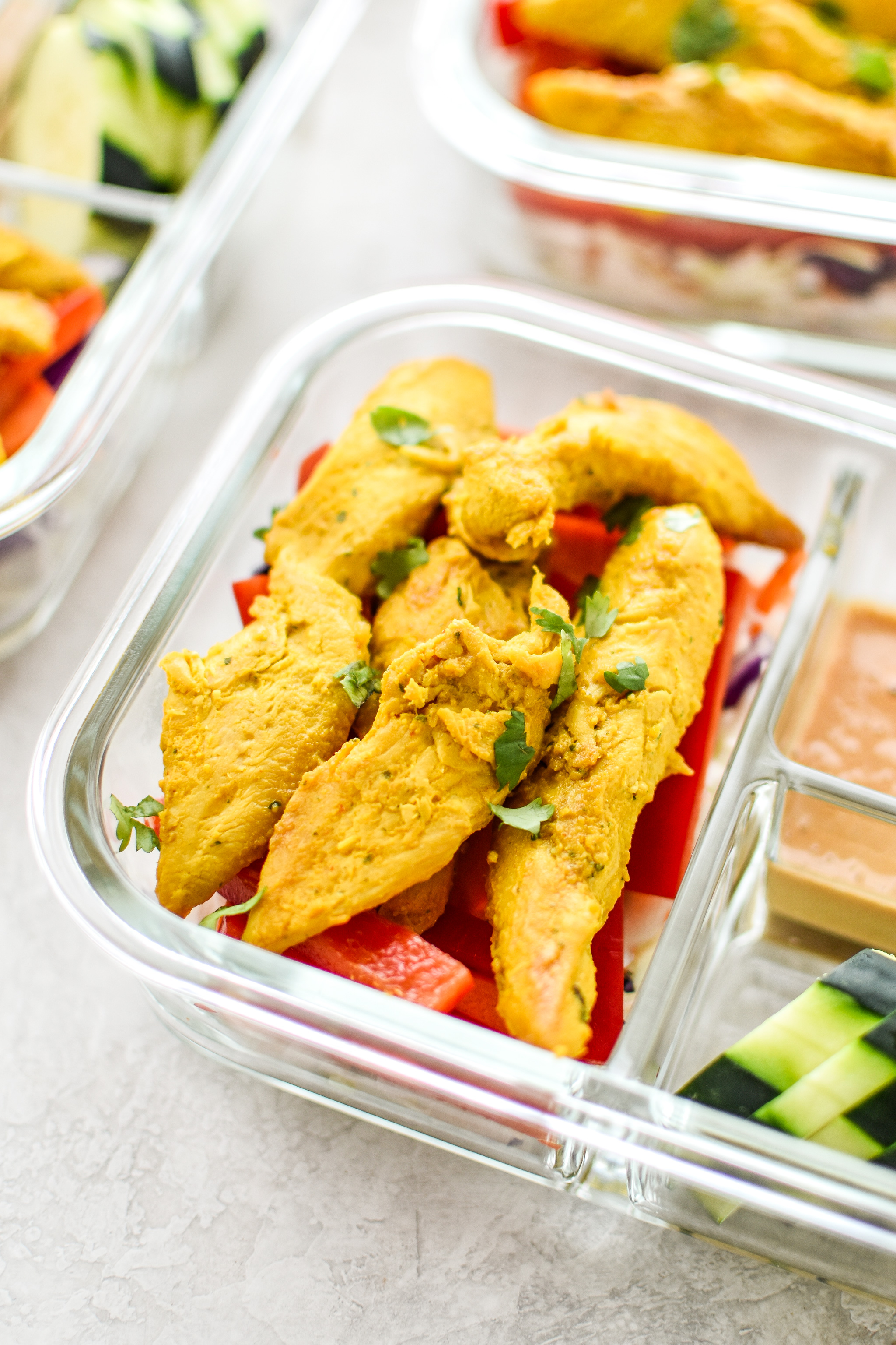 Meal Prep Satay Inspired Thai Chicken Salad Bowls portioned into meal prep containers, close up on the chicken.