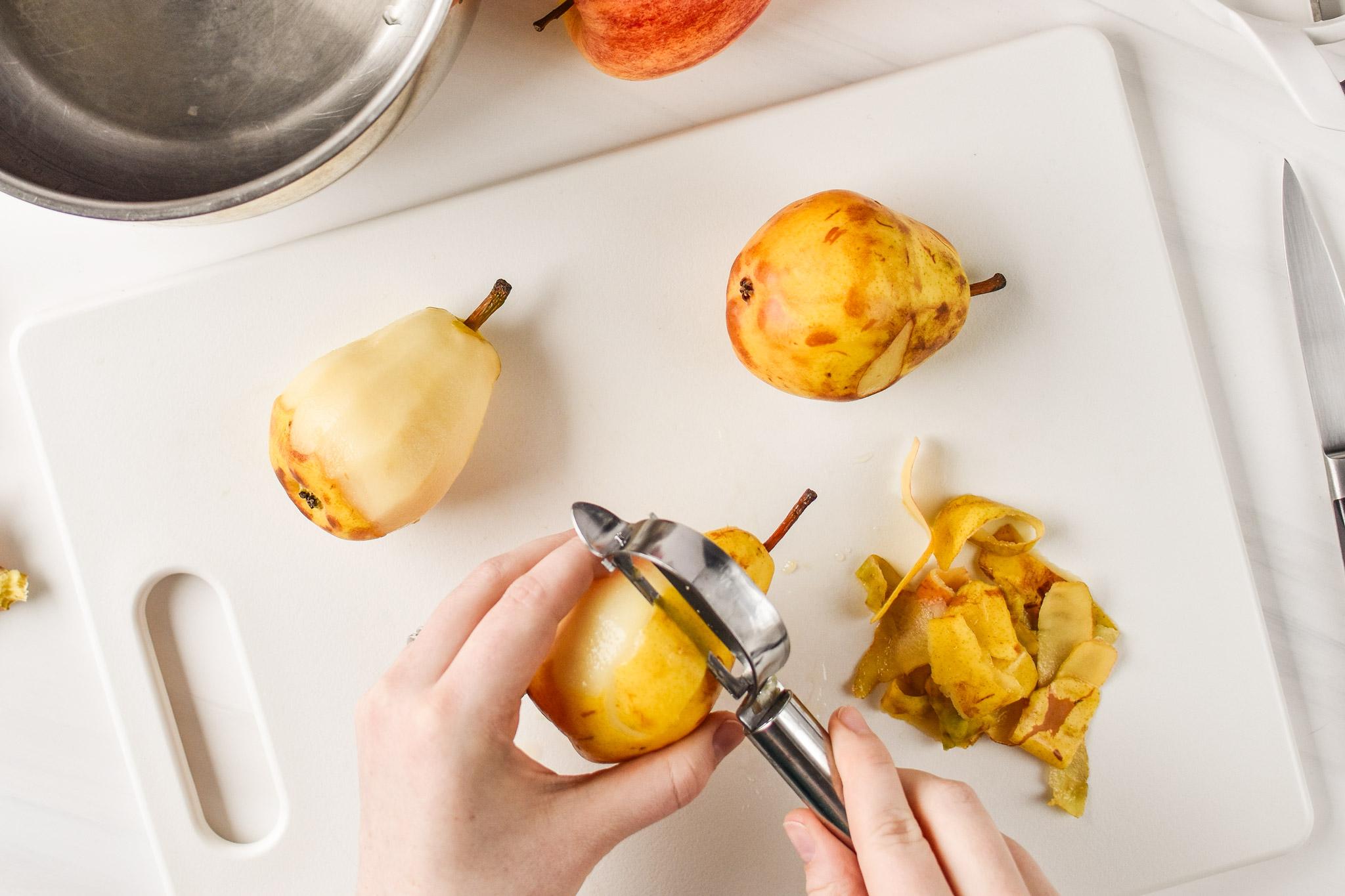 Peeling pears for Ginger Pear Cinnamon Applesauce