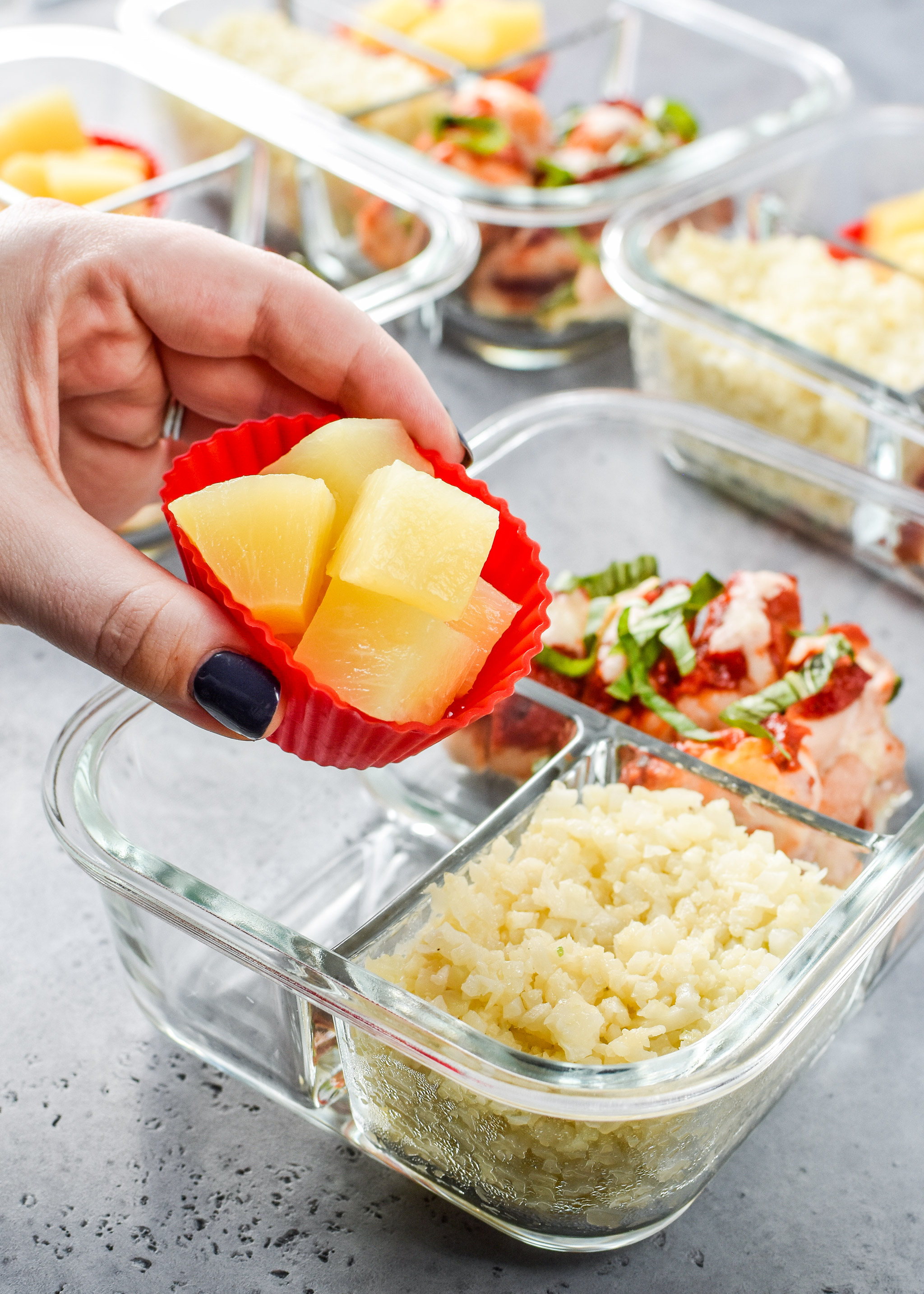 Pizza chicken roll ups meal prep with pineapple inside silicone baking containers for easy removal.