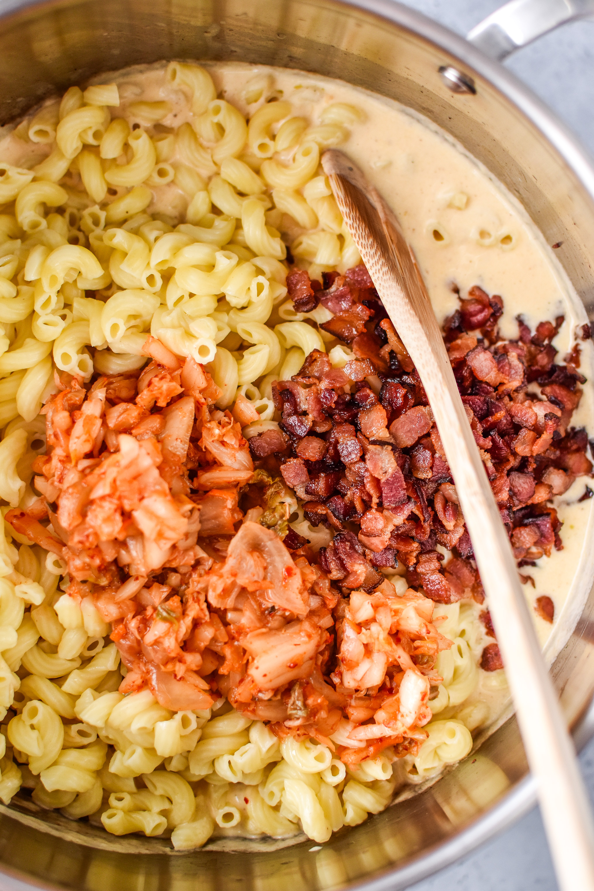 ingredients being mixed together to make the kimchi bacon greek yogurt mac and cheese