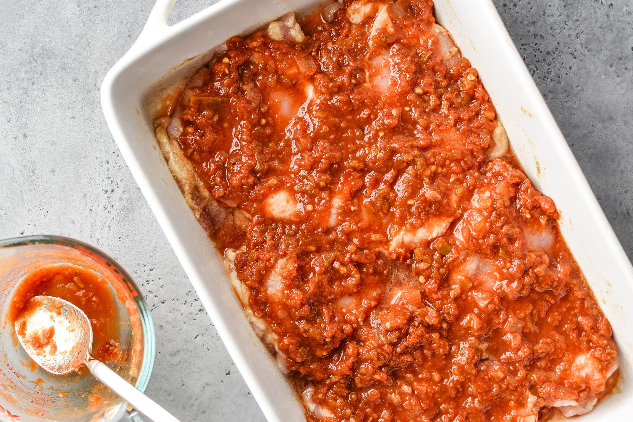 The chicken is covered in salsa for the baked salsa chicken thighs