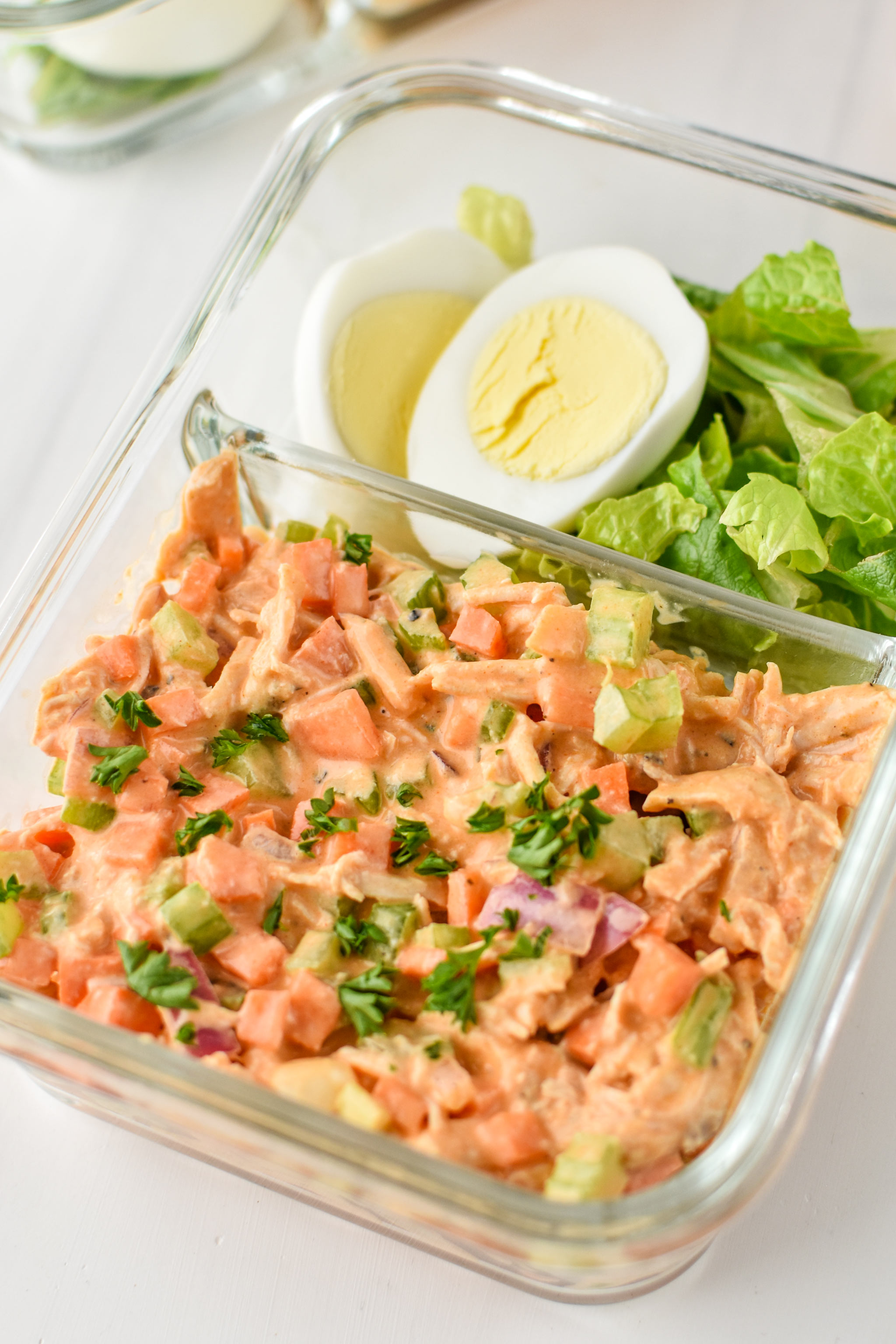 Easy Buffalo Chicken Salad meal prepped with a hard boiled egg and chopped romaine