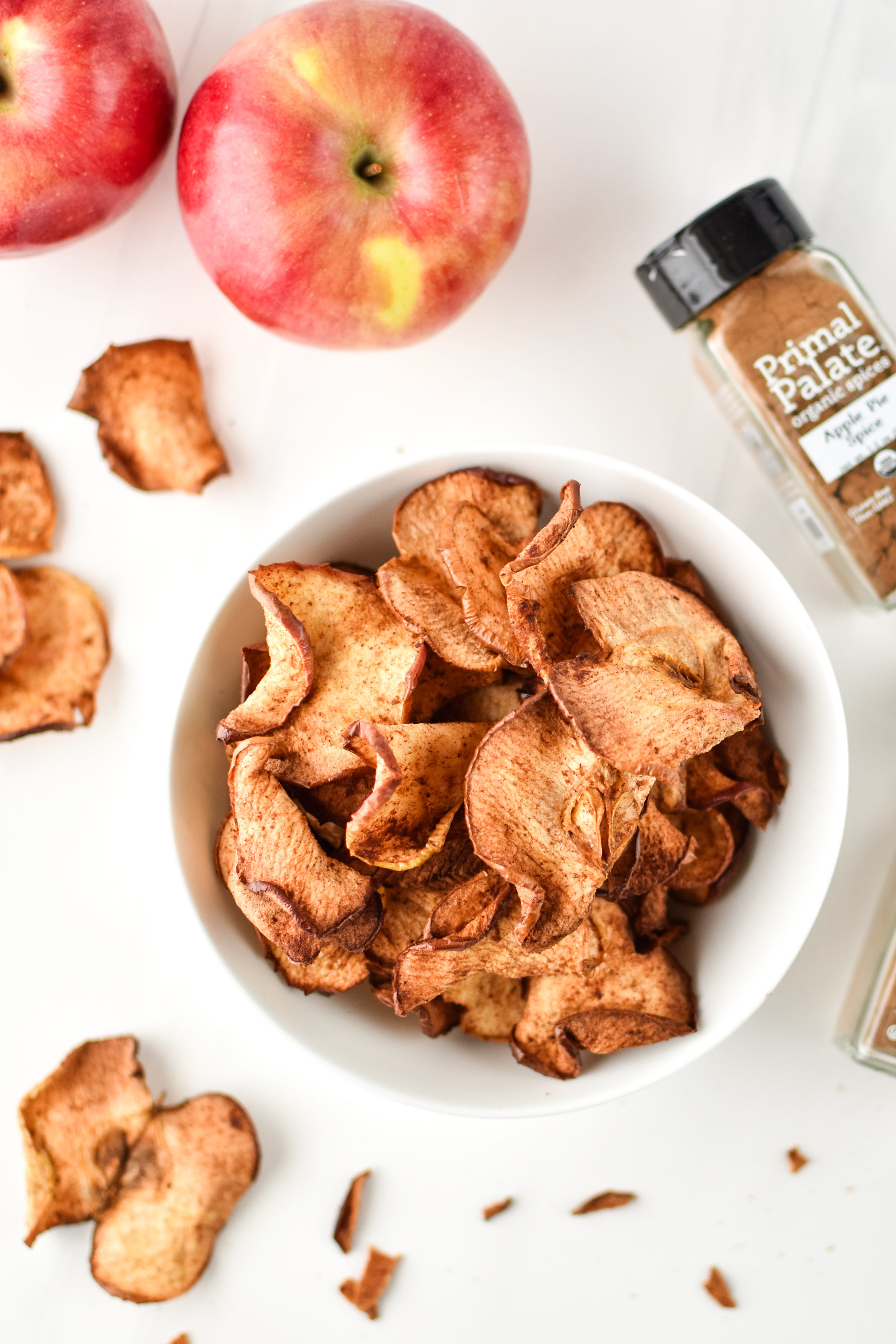 Apple chips photographed from above with apples for how to make apple chips in an air fryer.