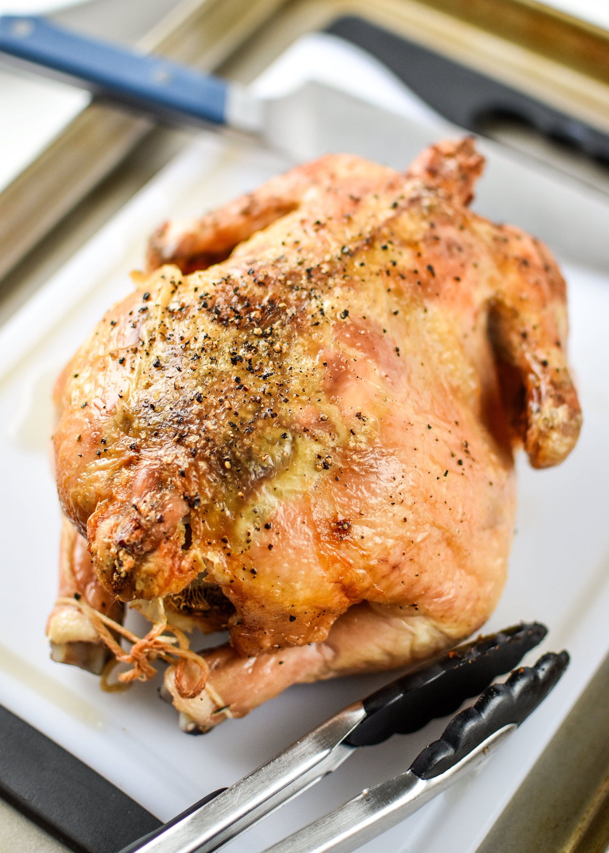 Simple whole roast chicken resting on a cutting board.
