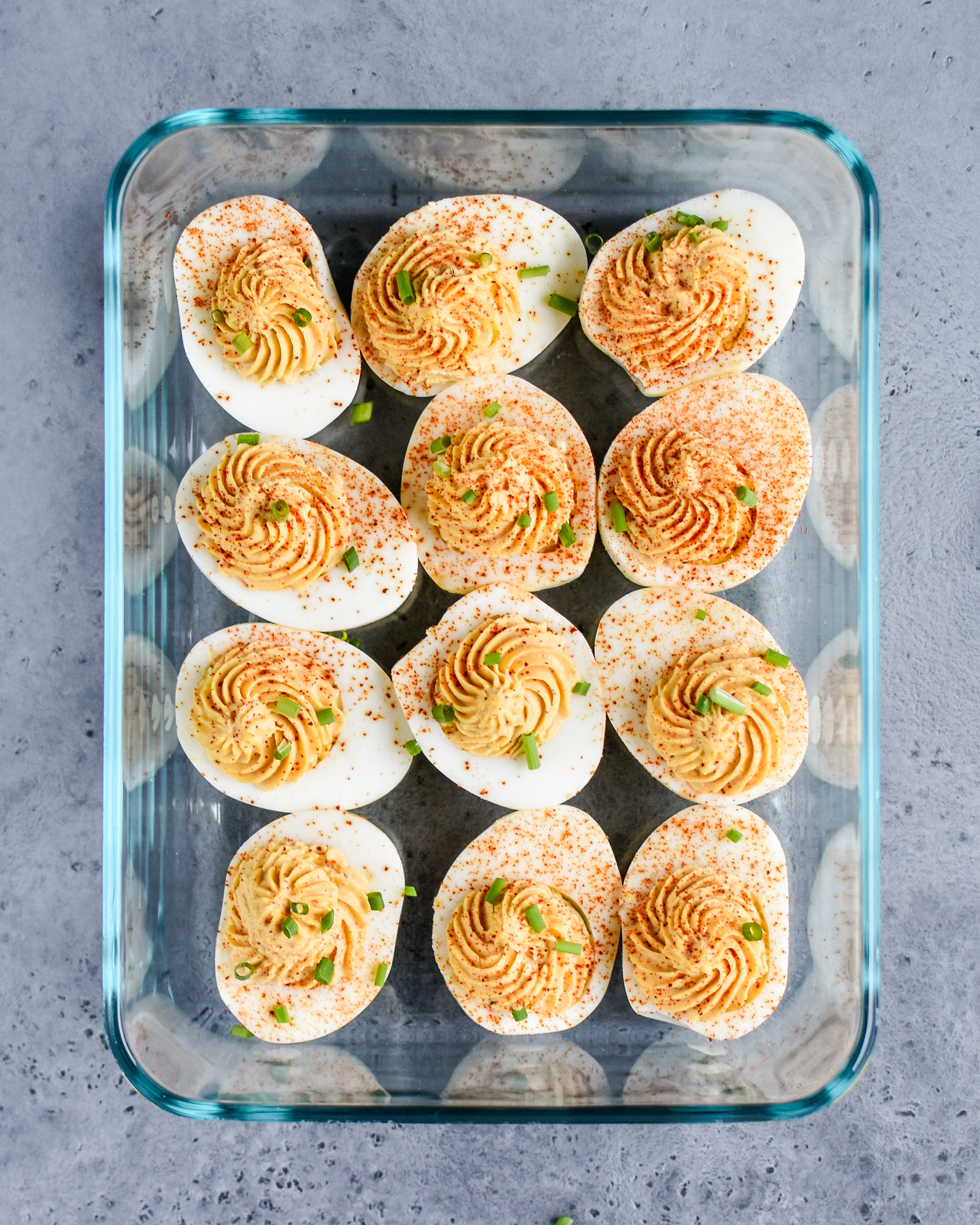 Buffalo deviled eggs stored in a rectangular pyrex container.