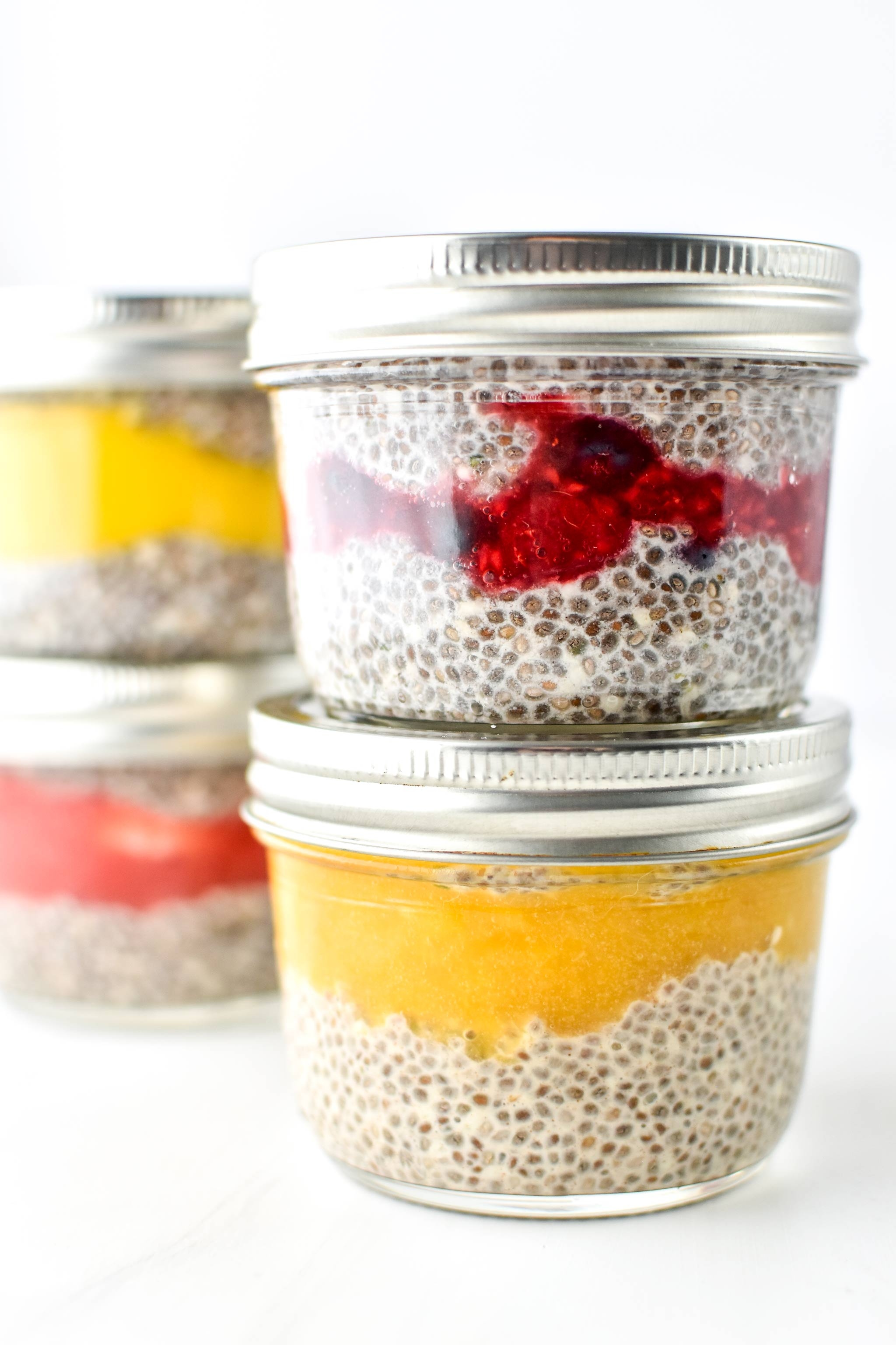 Chia pudding breakfast parfaits of different flavors in half pint mason jars.