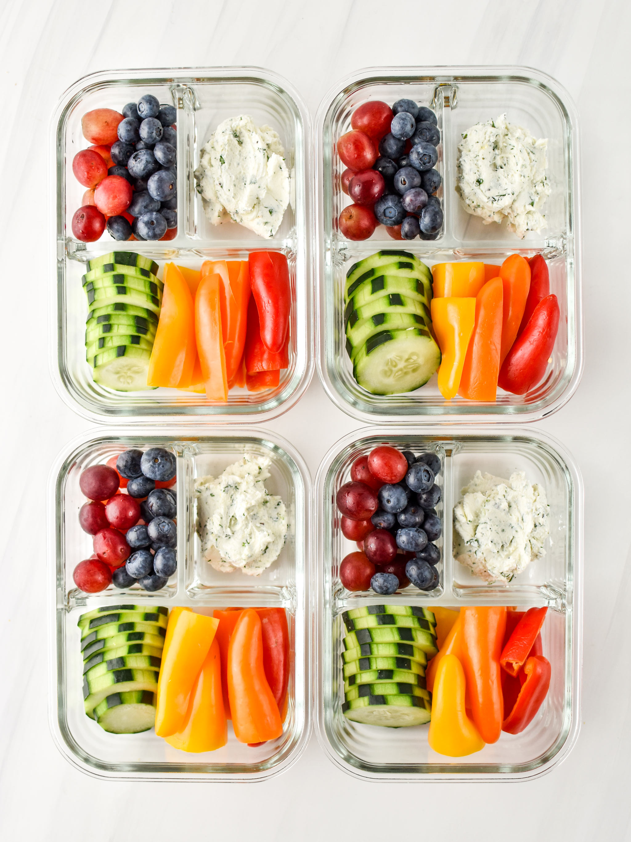 Herbed Goat Cheese Rainbow Snack Boxes in four meal prep containers pictured from above.