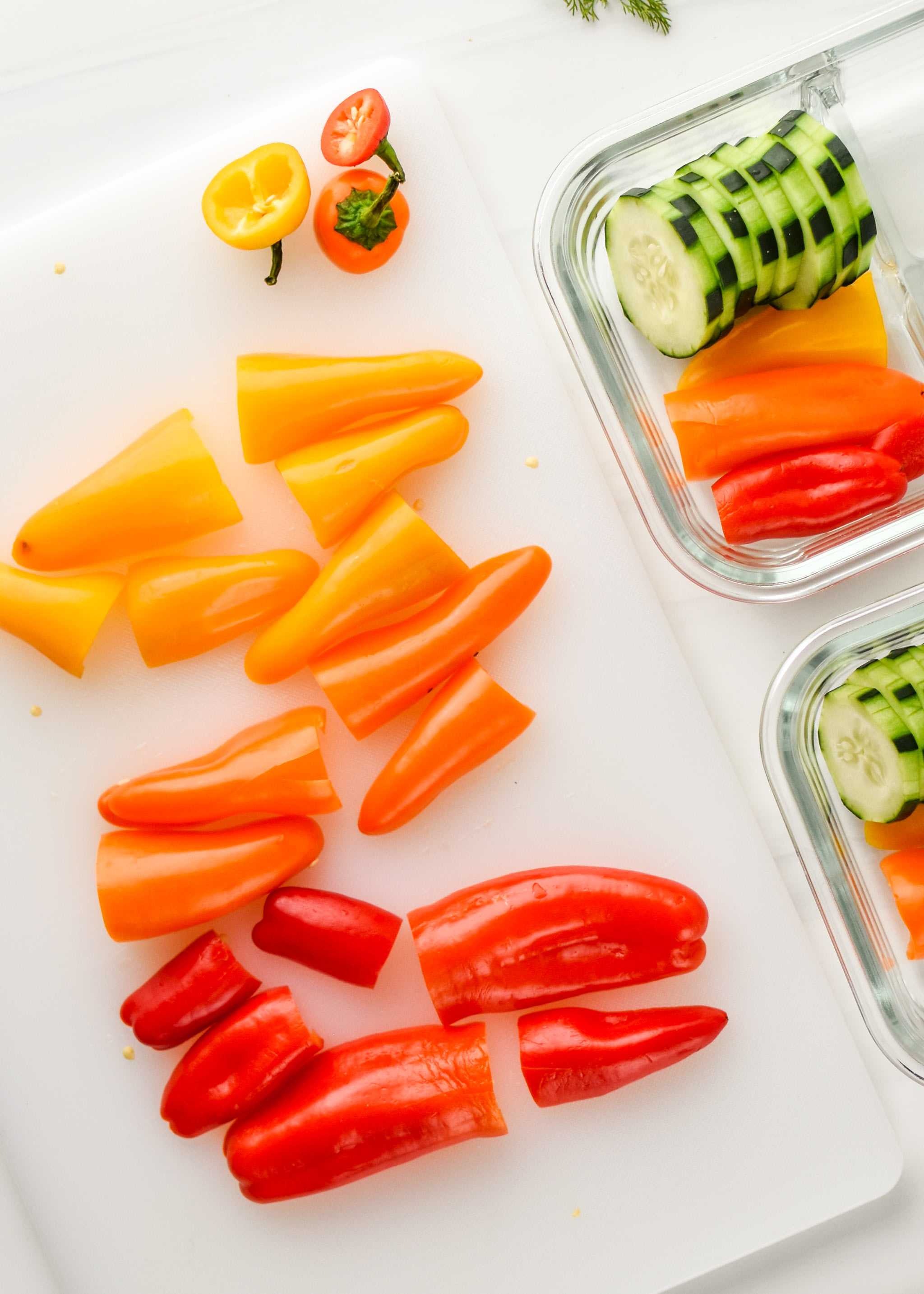 Rainbow mini peppers being cut up for the herbed goat cheese rainbow snack boxes.