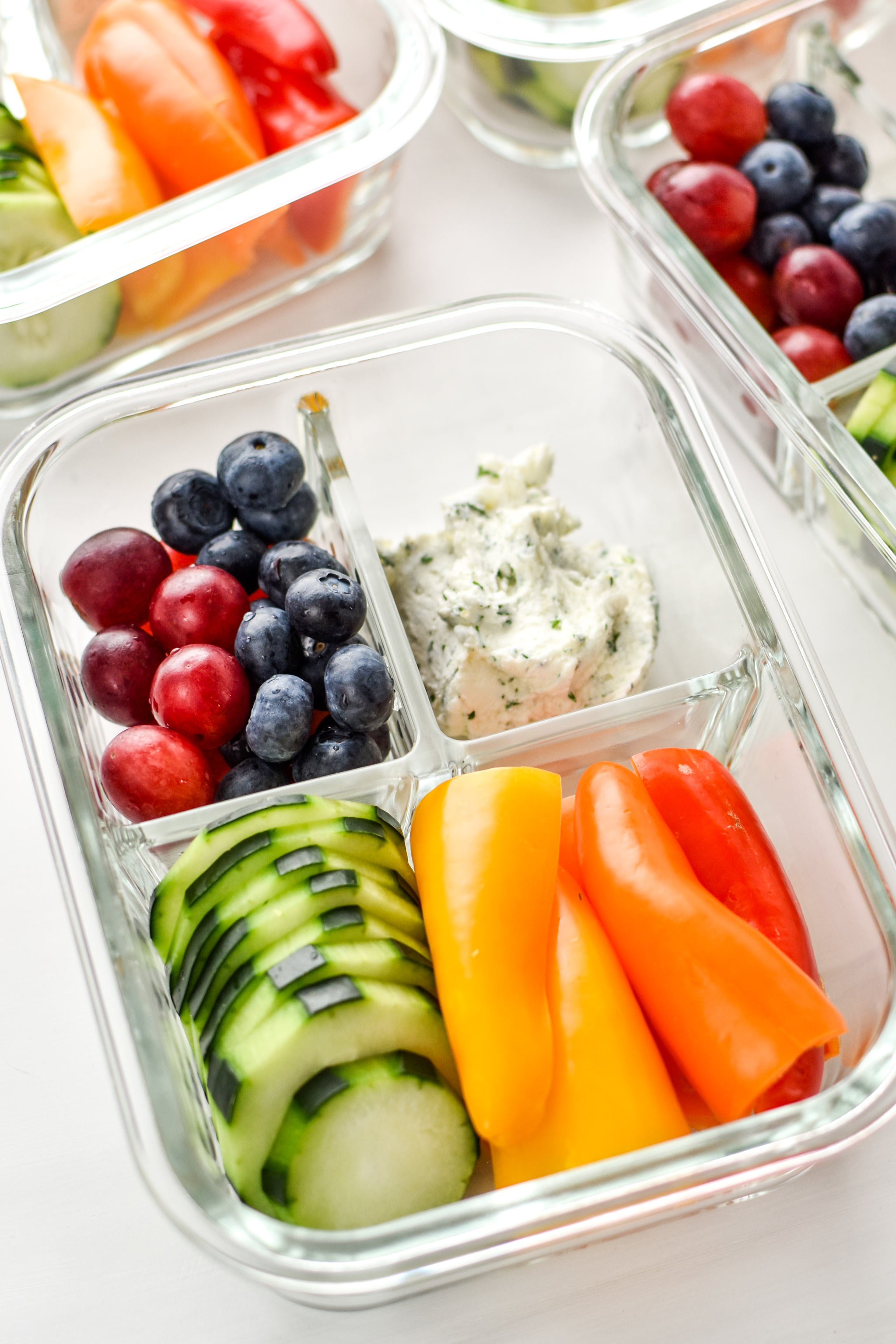 An herbed goat cheese rainbow snack box with fruits and veggies.