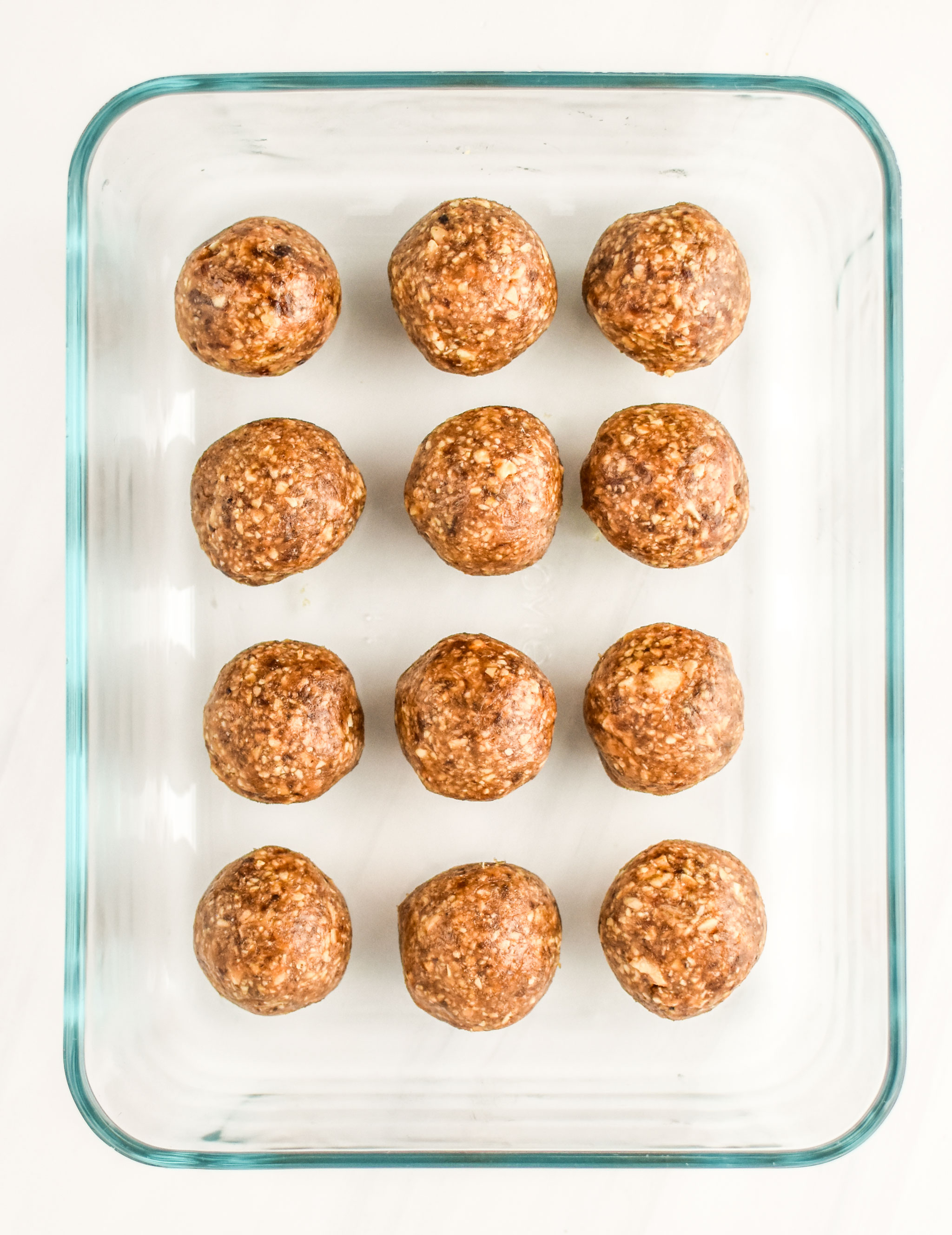 Peanut butter cookie balls stashed in a Pyrex container for storage.