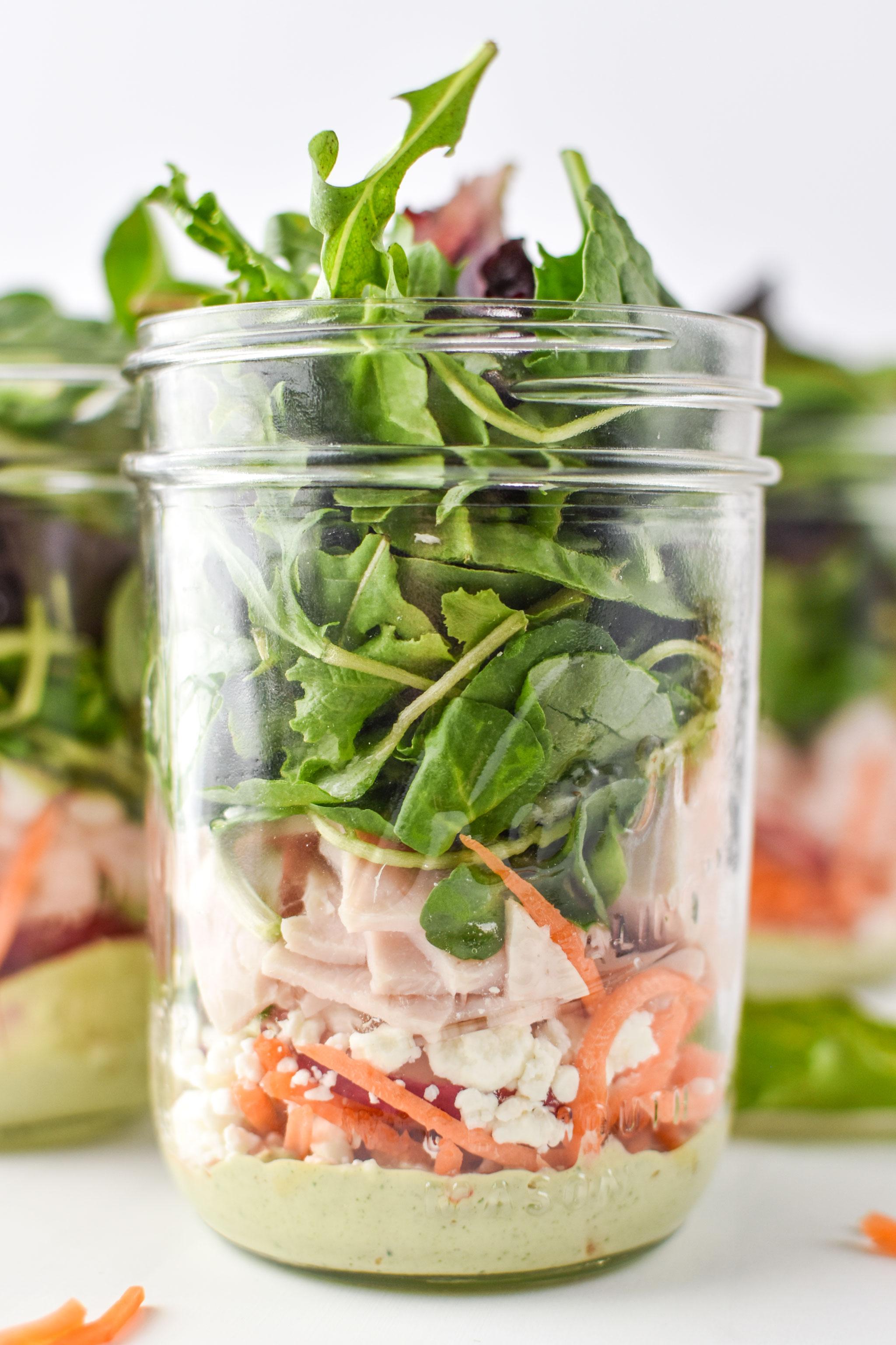 Cilantro lime tahini dressing at the bottom of these mason jar salads