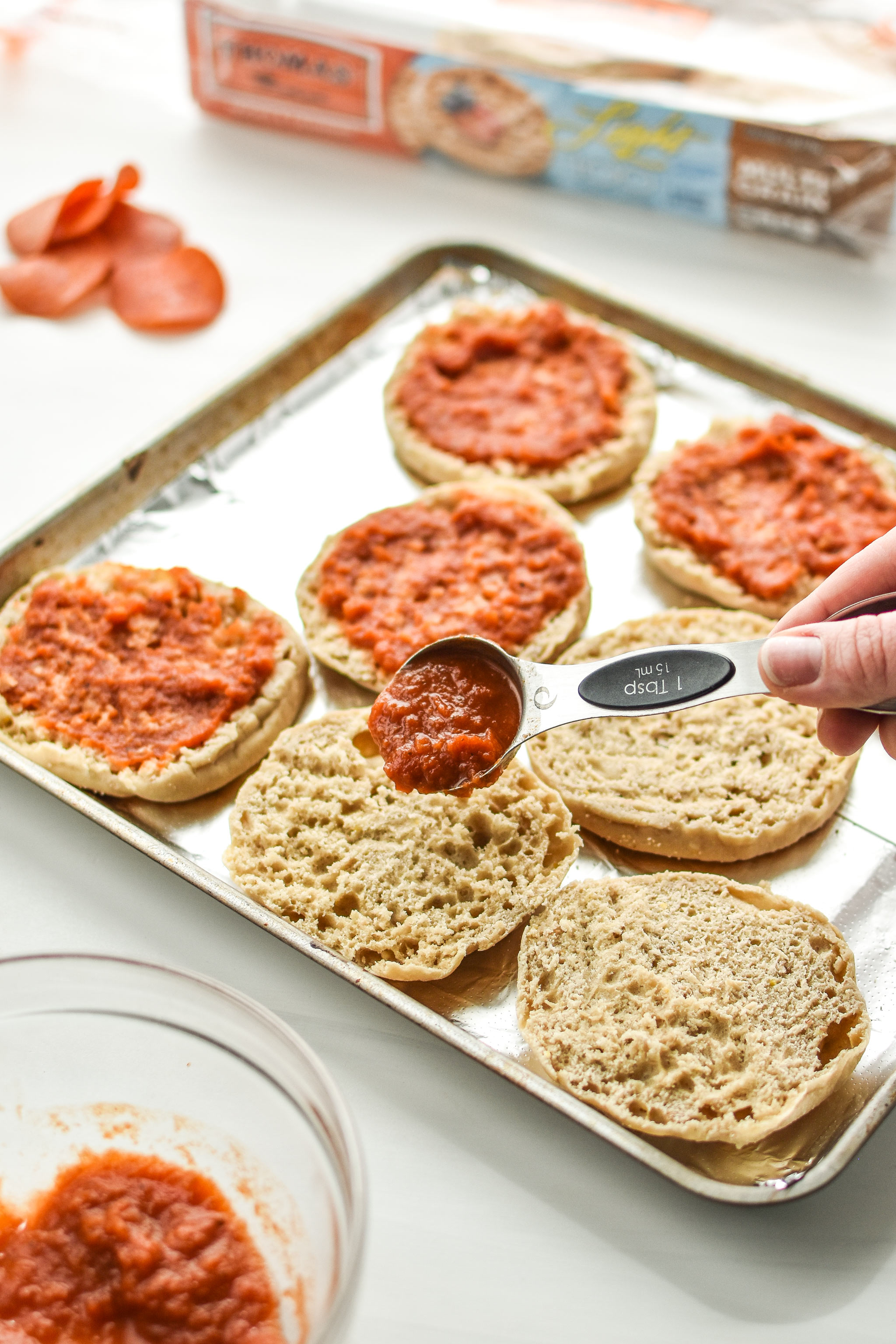 Adding sauce to the english muffins for the english muffin mini pizza meal prep