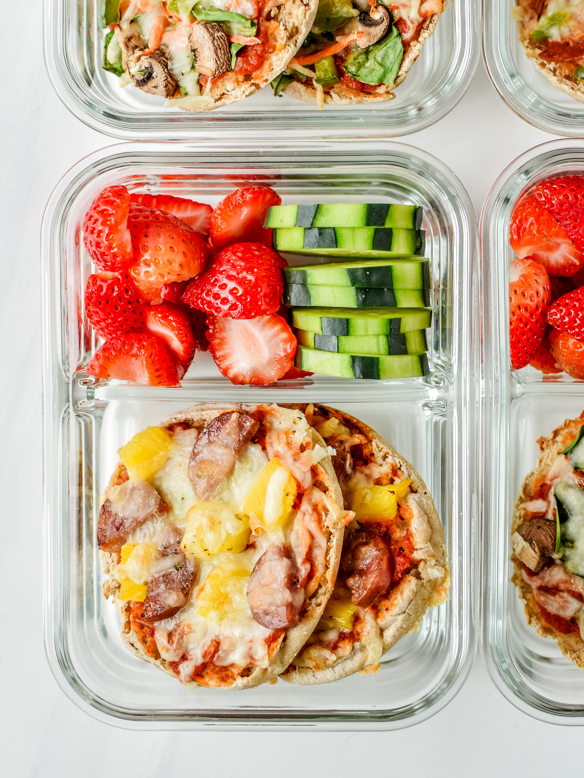 English muffin mini pizzas meal prep - meaty pineapple pictured with fresh cut cucumbers and strawberries