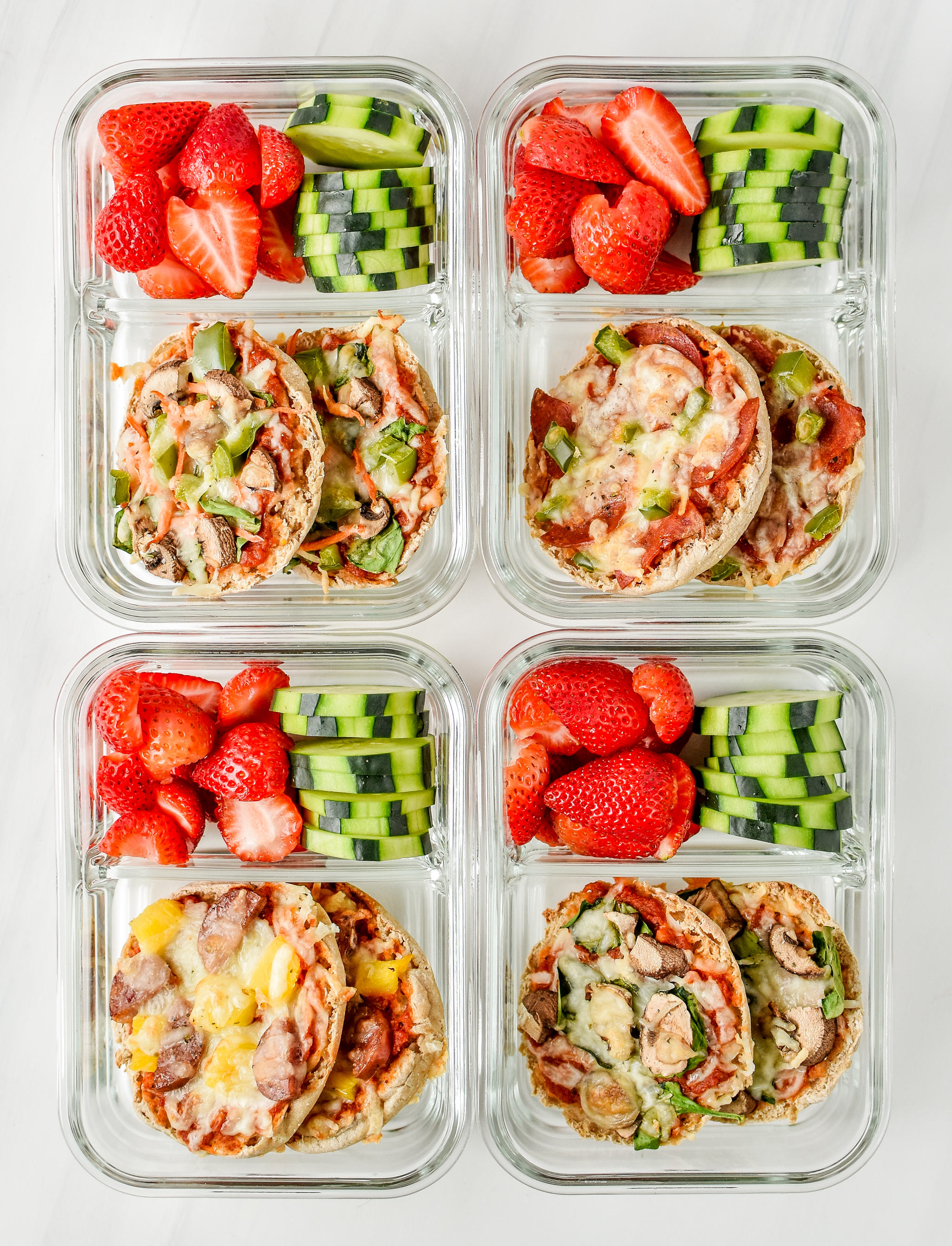 English muffin mini pizzas meal prep pictured from above in meal prep containers with fresh cut strawberries and cucumbers.