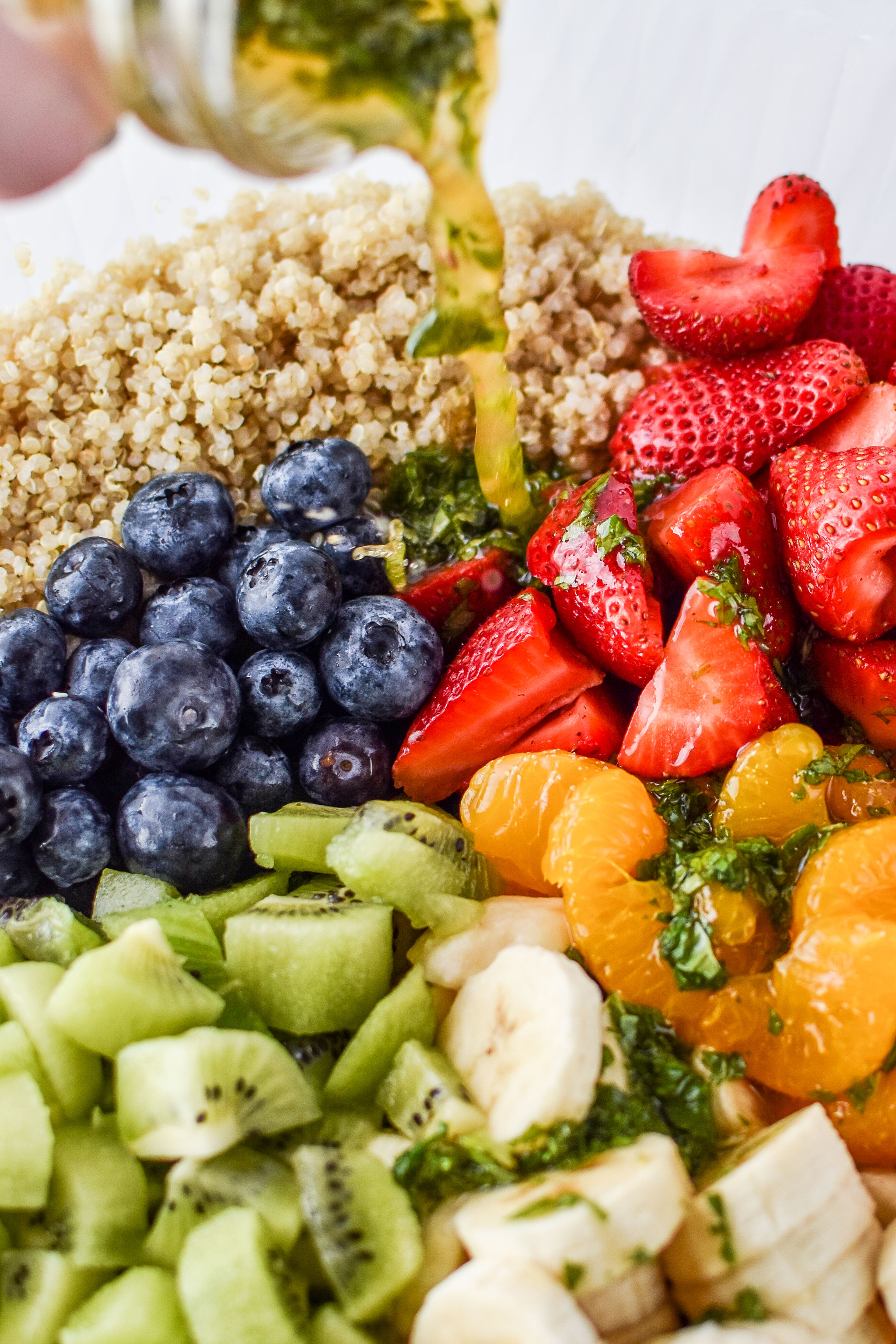 pouring the honey lime mint dressing over the fruit for the mint quinoa fruit salad
