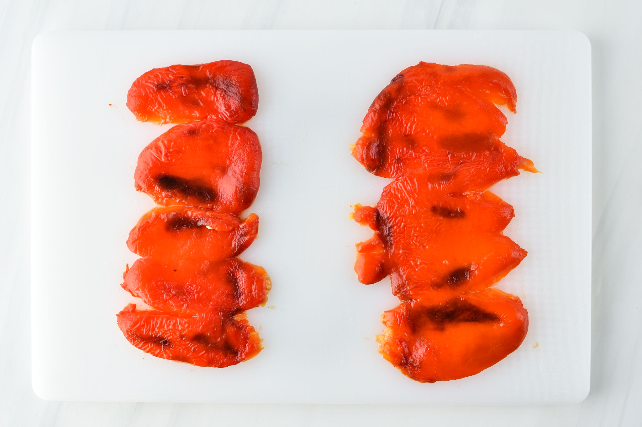 two red bell peppers roasted with stem, seeds and peel removed, laid out on a cutting board