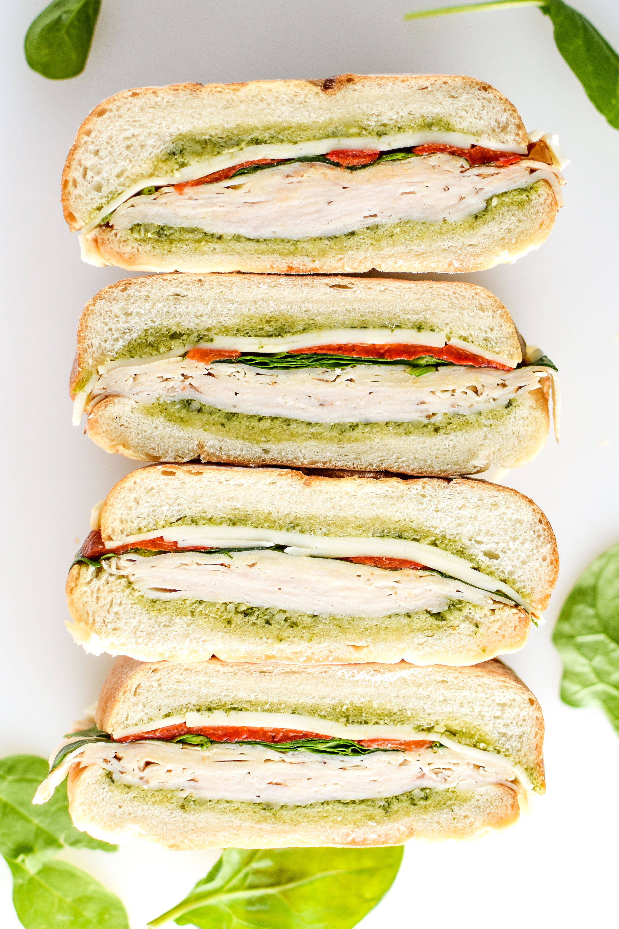 Pesto chicken overnight pressed sandwiches cut into 4 with inside facing up