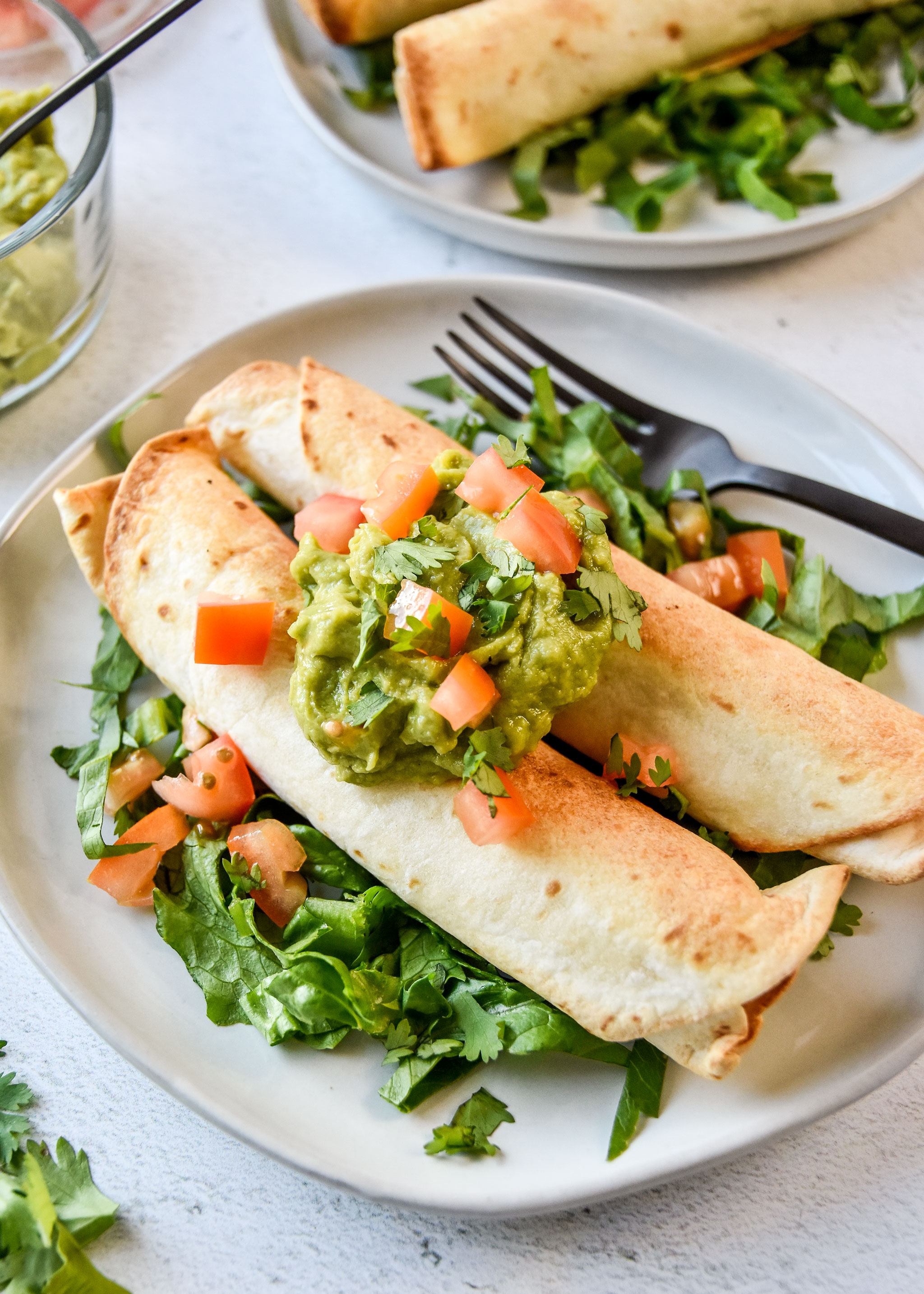 air fryer chicken taquitos topped with guacamole, tomatoes and cilantro