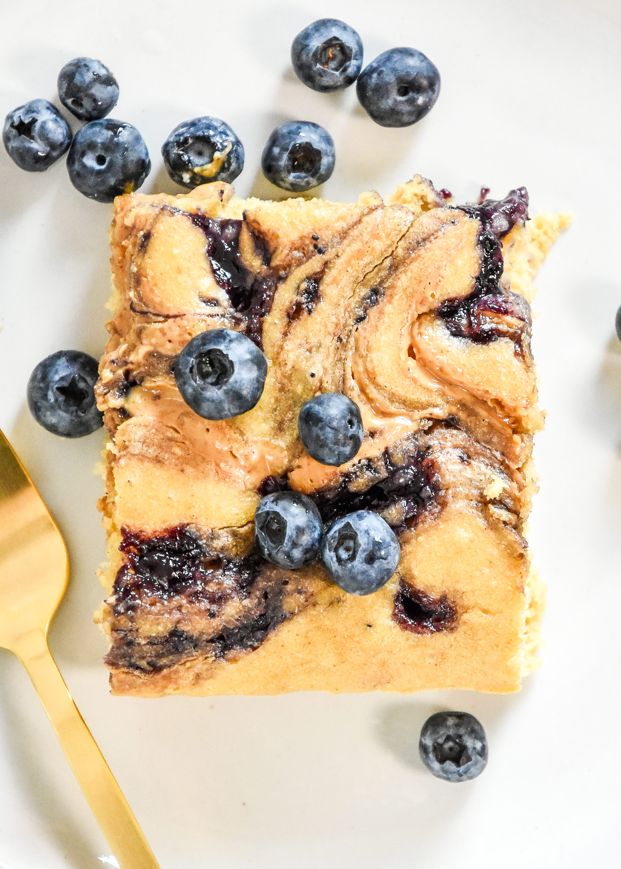 a perfect slice of peanut butter and jelly baked pancakes with blueberries on top