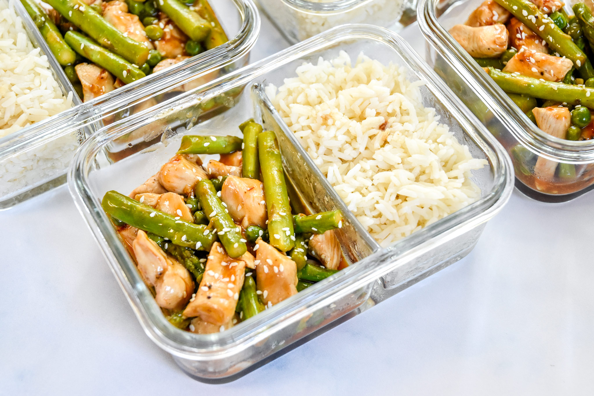 meal prep spicy chicken and asparagus in glass meal prep containers
