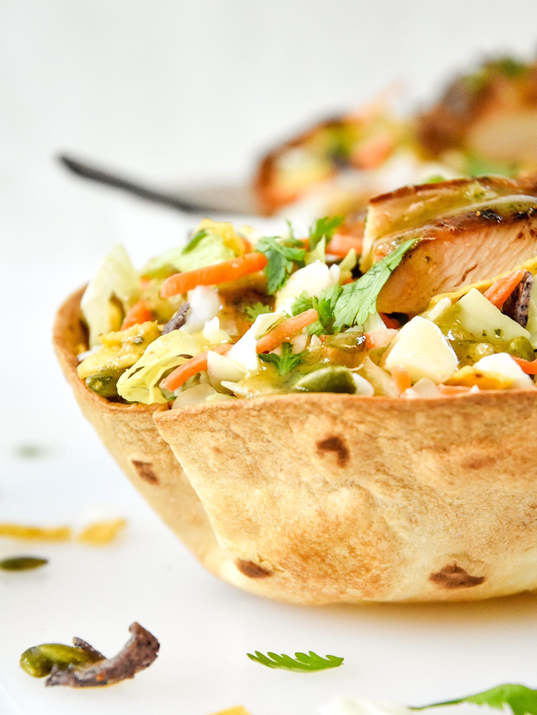 delicious taco salad with chicken in an air fryer flour tortilla bowl.